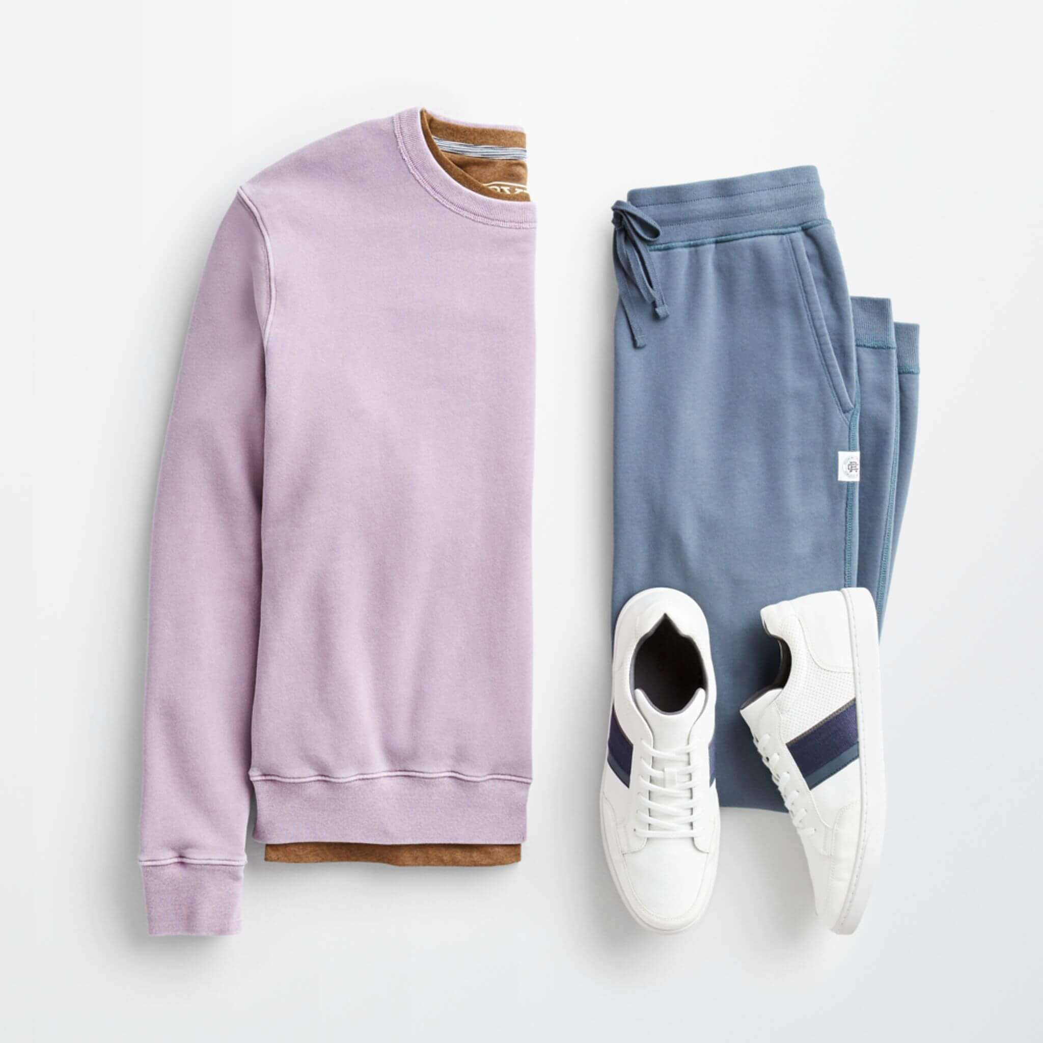 Stitch Fix Men's outfit laydown featuring a light purple crewneck sweatshirt over a brown t-shirt, next to blue sweatpants and white sneakers.