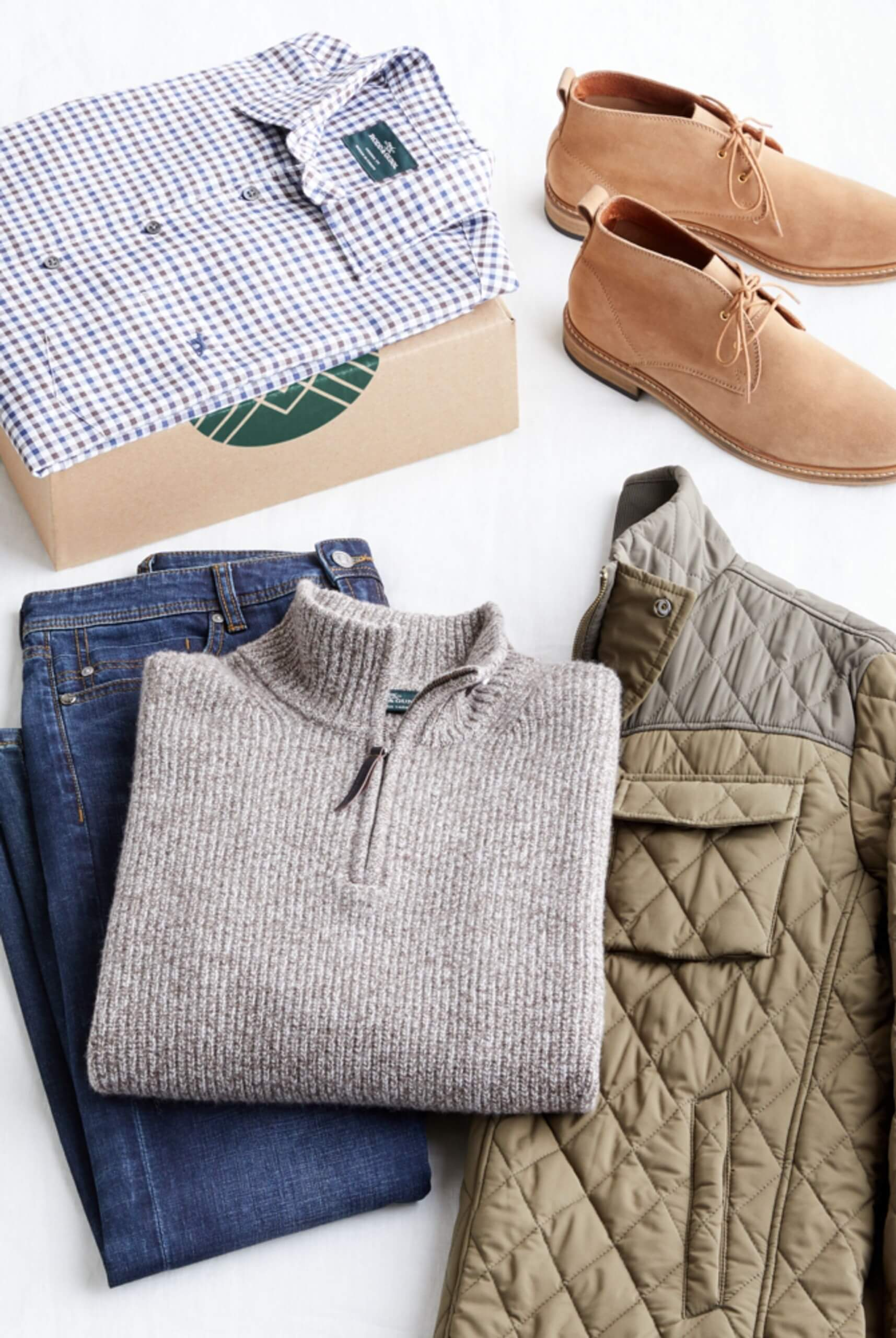 Stitch Fix Men's outfit laydown featuring a quarter-zip sweater over dark wash jeans and quilted jacket, next to tan chukkas and checkered woven shirt sitting on a Stitch Fix delivery box.