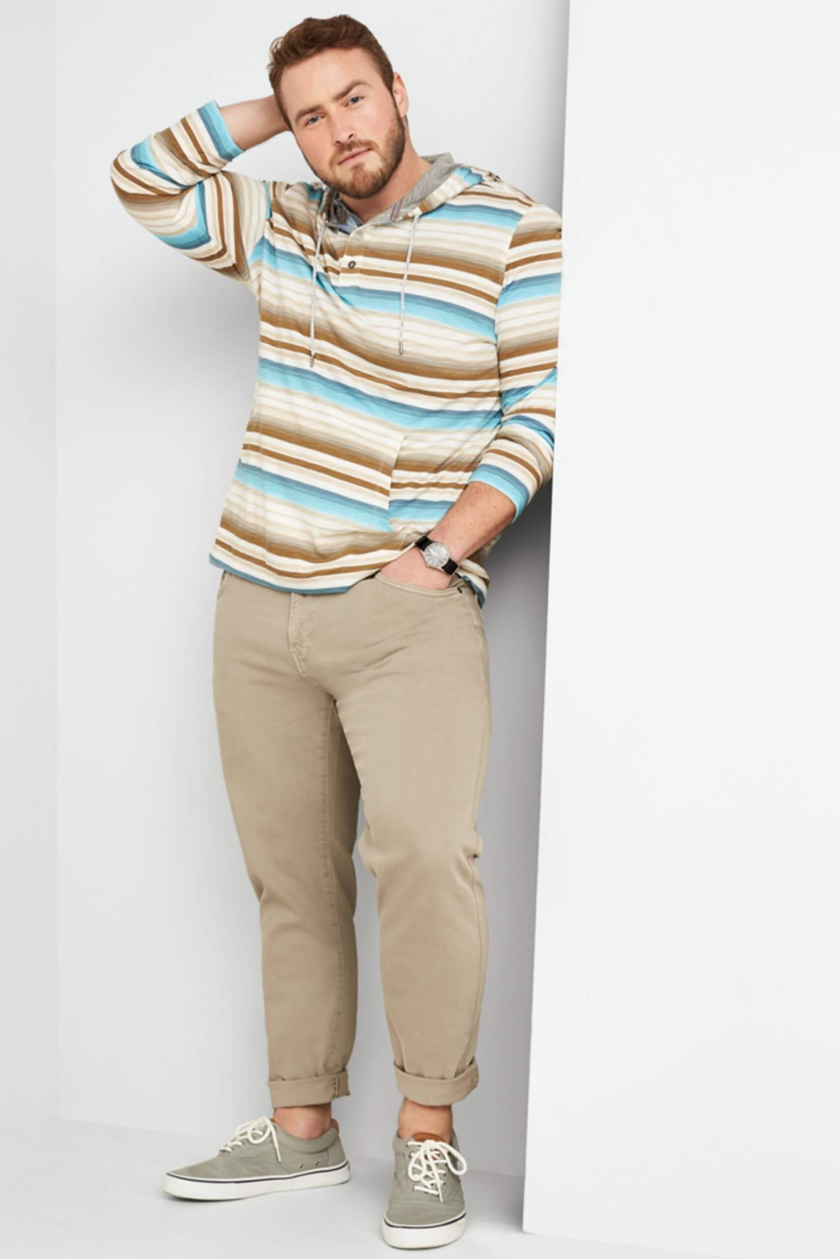 Stitch Fix Men's model wearing multi-colored striped hoodie over a light grey henley with khaki slim-fit jeans and grey canvas sneakers.