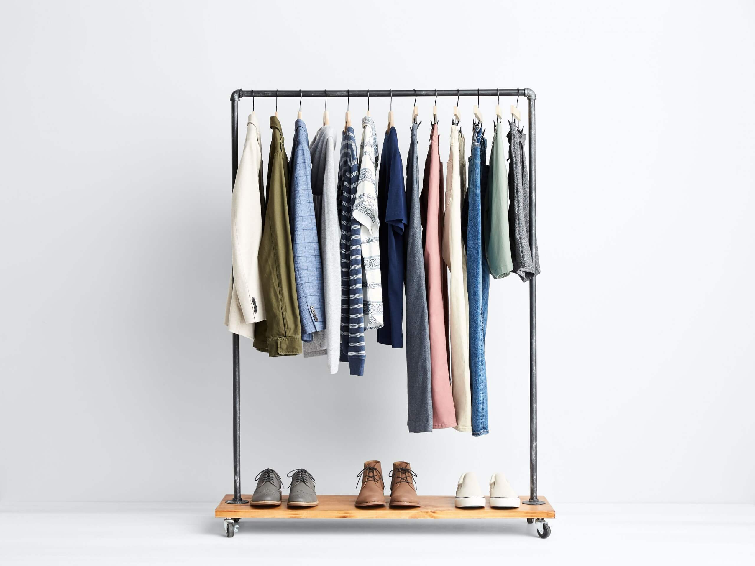 Stitch Fix Men's rack image featuring beige blazer, green military jacket, blue button-down shirt, grey hoodie, striped shirts, navy polo, grey pants, pink pants, khaki pants, blue jeans, green shorts and grey shorts hanging above grey sneakers, brown chukkas and white sneakers.
