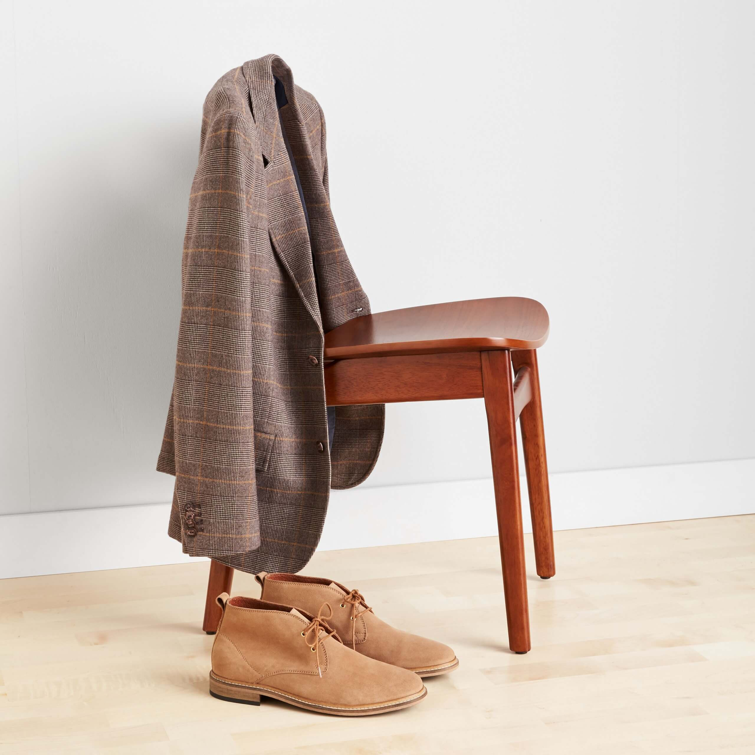 Stitch Fix Men's brown plaid jacket hanging over a wooden chair, next to tan chukkas on the floor.