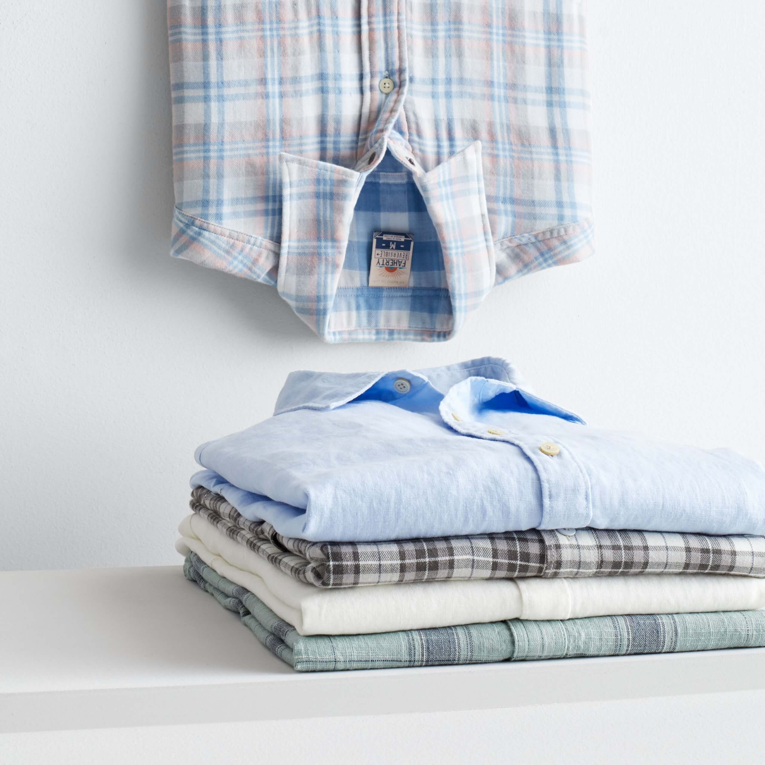 Stitch Fix Men's folded stack of button-down shirts in various shades of blue, cream and grey and one blue plaid shirt hanging upside down.