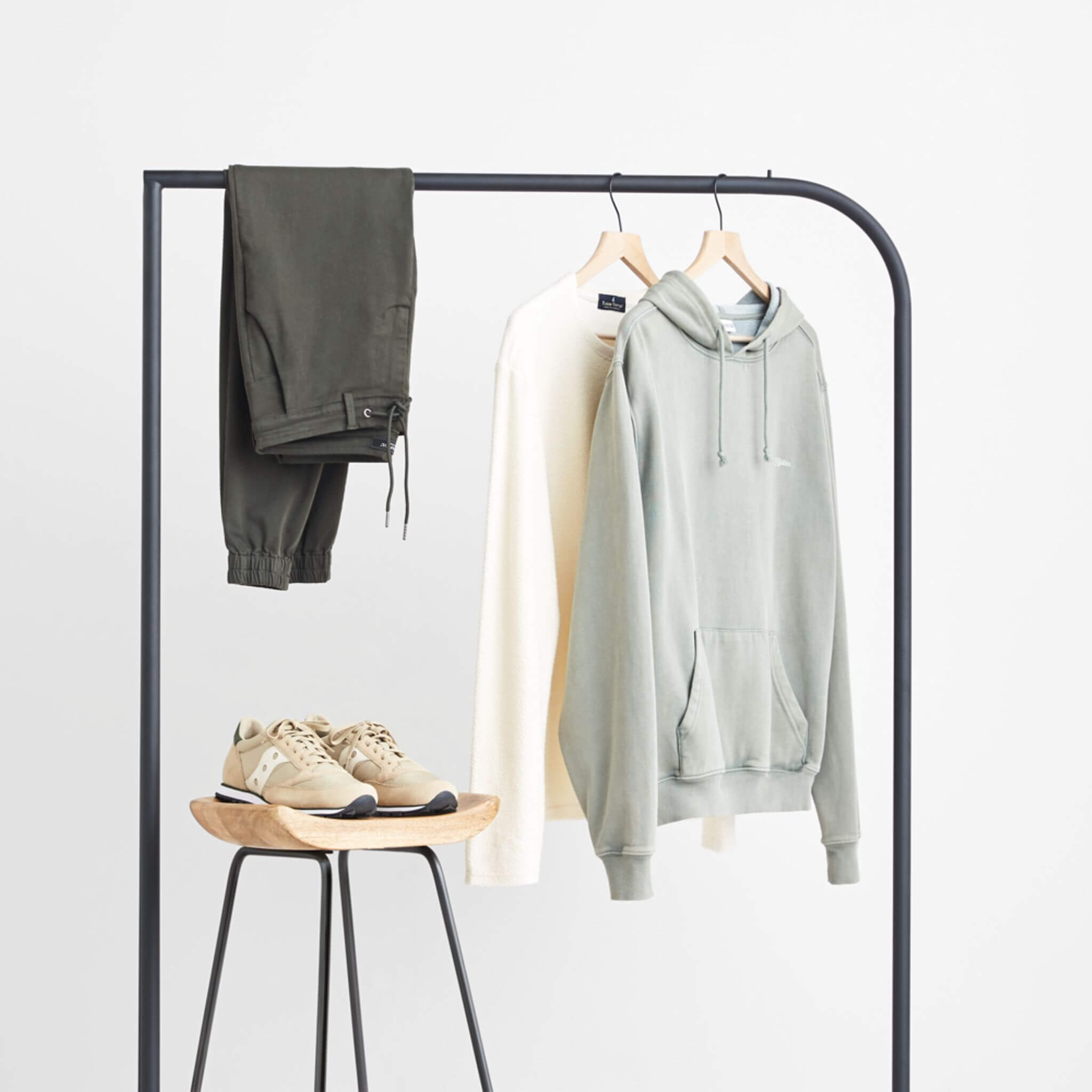 Stitch Fix Men's grey hoodie, cream french terry pullover and dark grey woven joggers hanging on a black rack next to tan sneakers sitting on a wooden stool.
