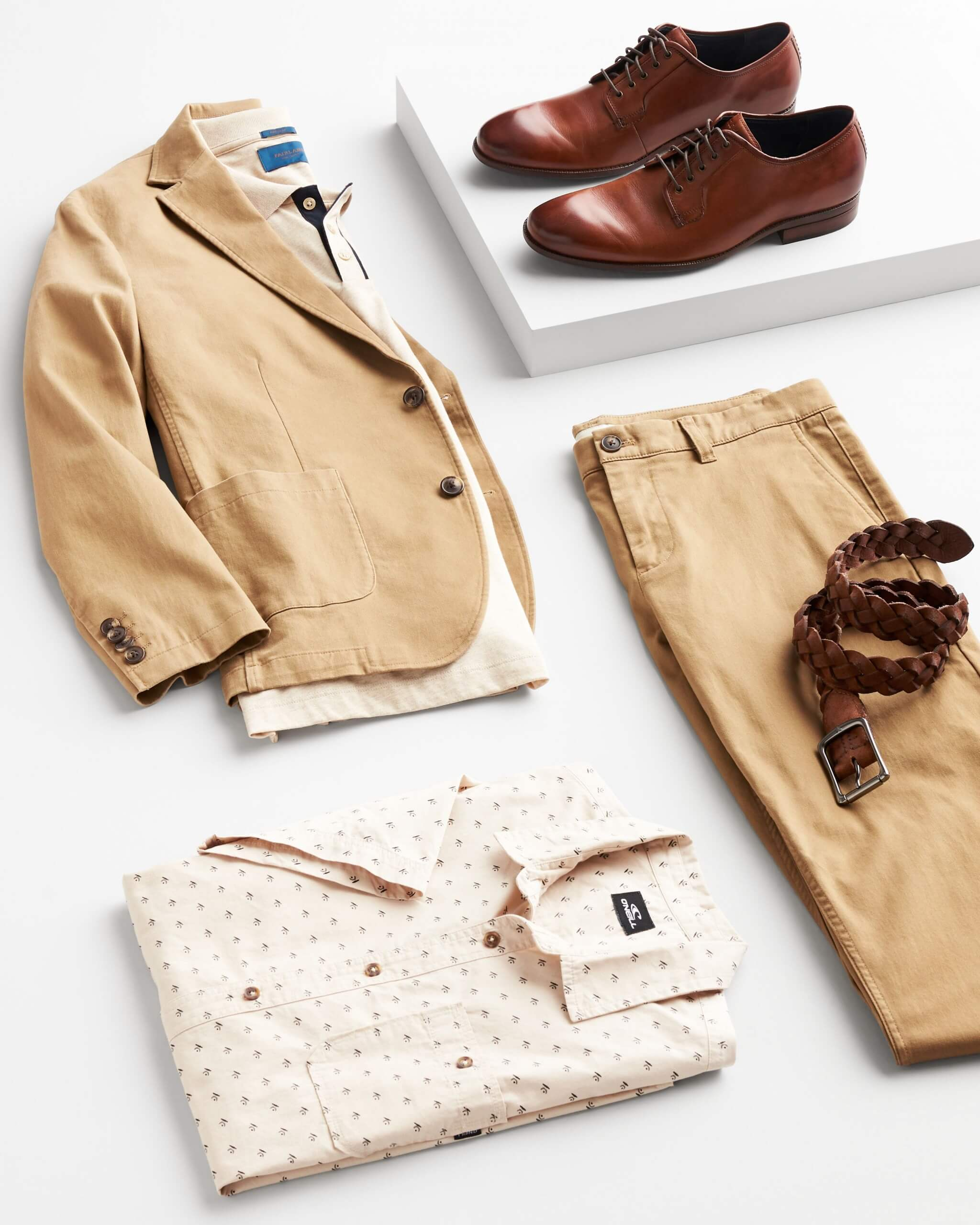 Stitch Fix Men's outfit laydown featuring cognac Oxford dress shoes on white block next to tan blazer over cream polo shirt, khaki chinos, brown belt and tan folded button-front shirt.