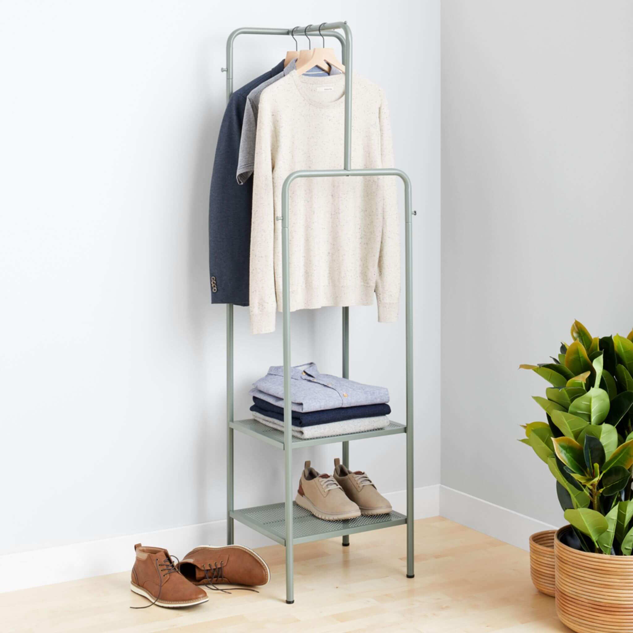 Stitch Fix Men's cream crewneck pullover, grey polo and navy blazer hanging on grey rack, with light button-down shirts folded and tan leather sneakers on grey shelves, next to brown chukkas on the floor.