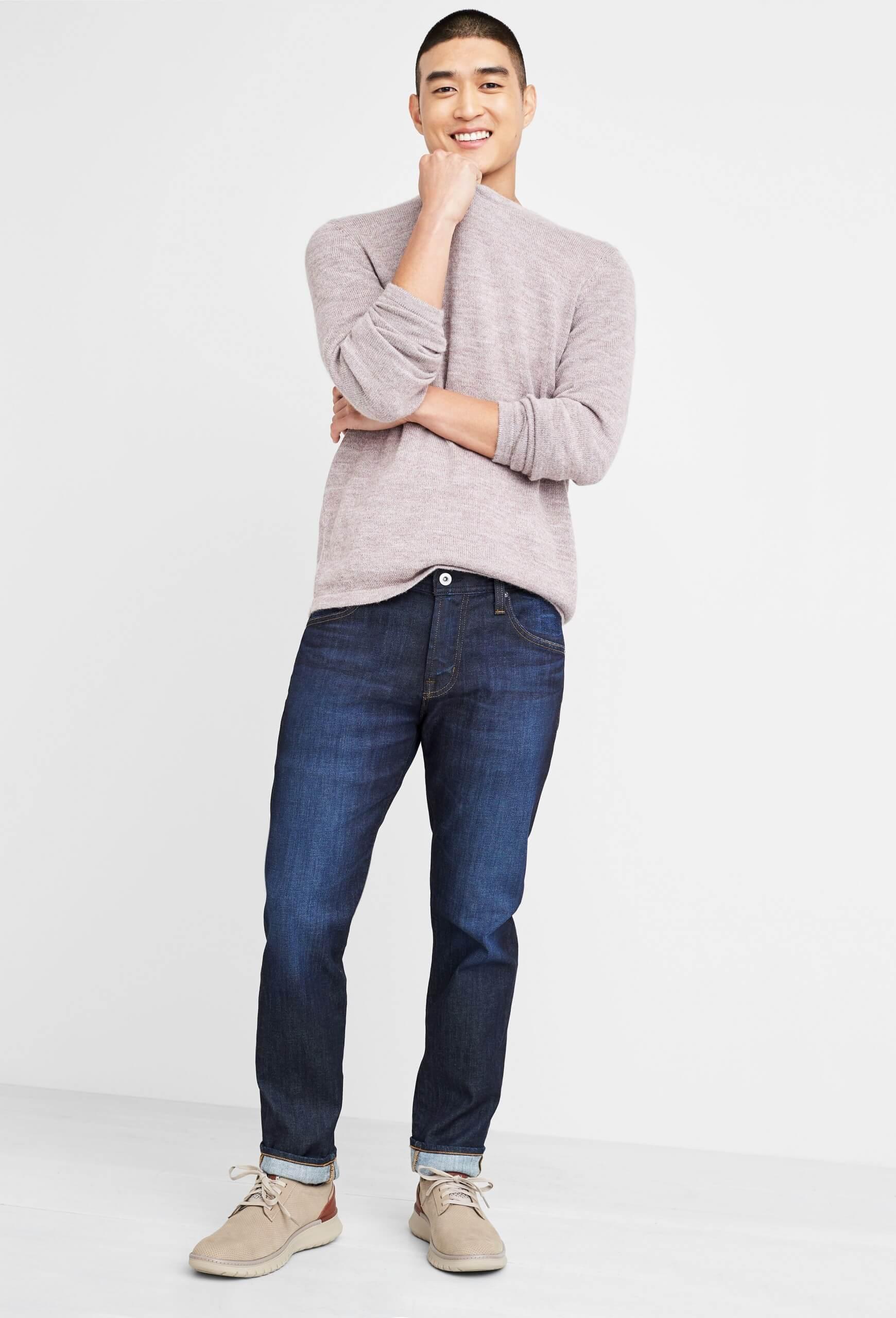 Stitch Fix Men's model wearing dark wash jeans, beige crewneck sweater and beige leather sneakers.