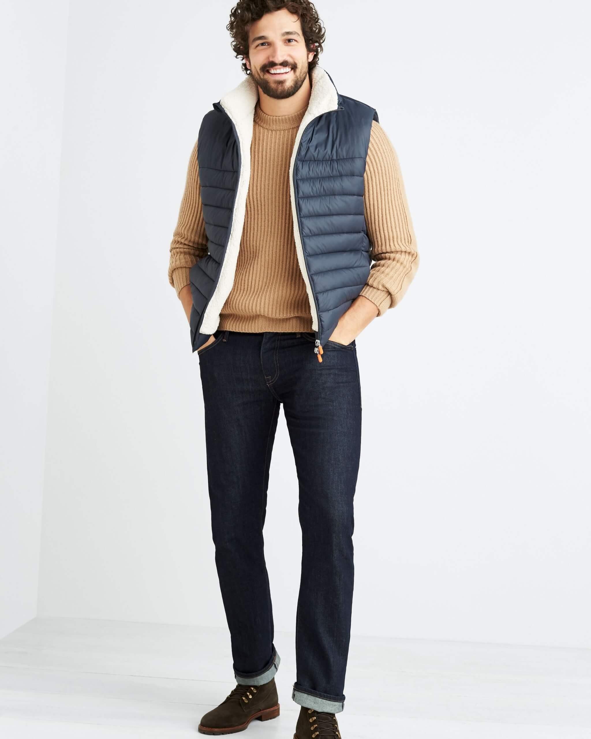 Stitch Fix Men's model wearing dark wash jeans, brown crewneck sweater, navy puffer vest and brown boots.