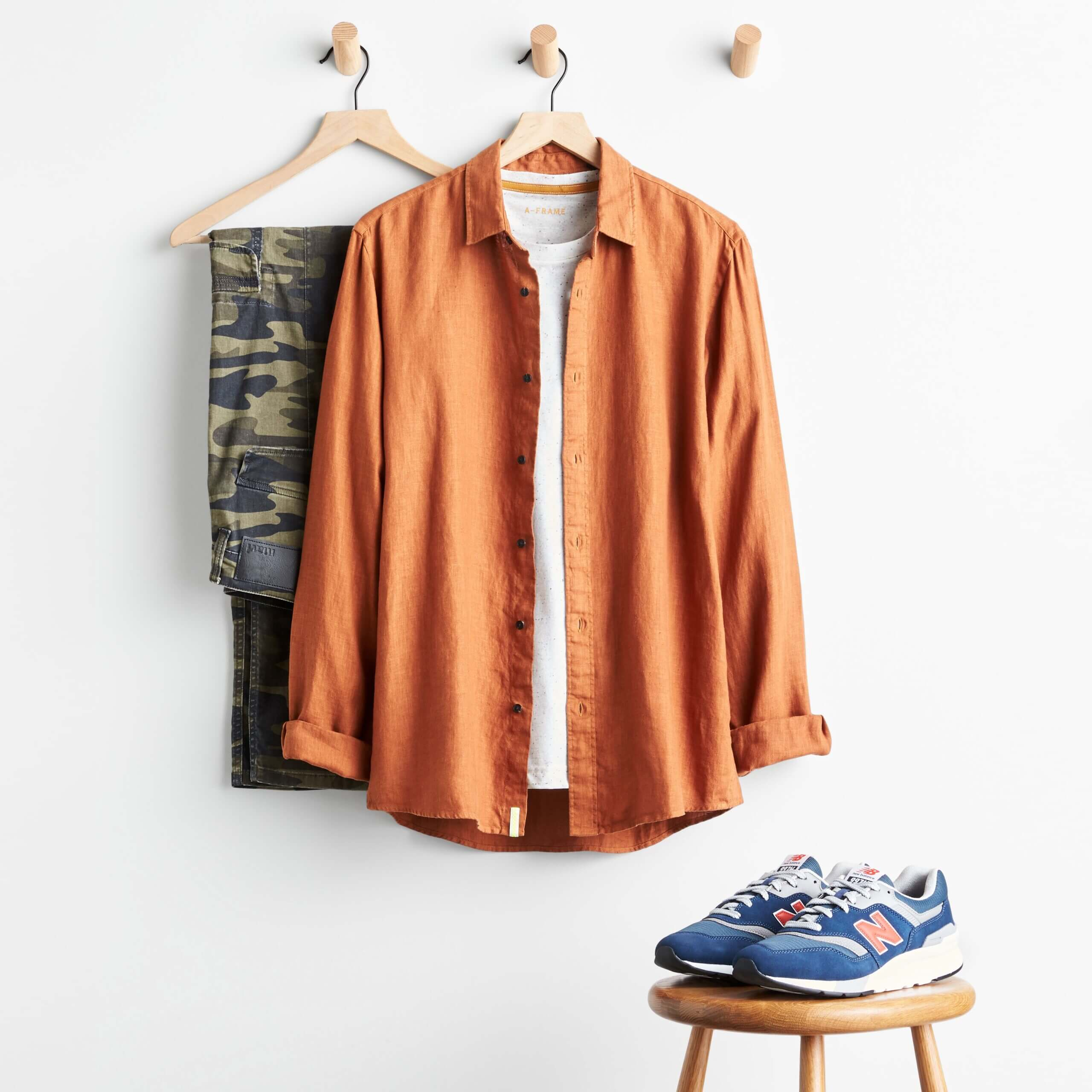 Stitch Fix Men's camouflage pants, white T-shirt, orange button-up and navy and orange sneakers.