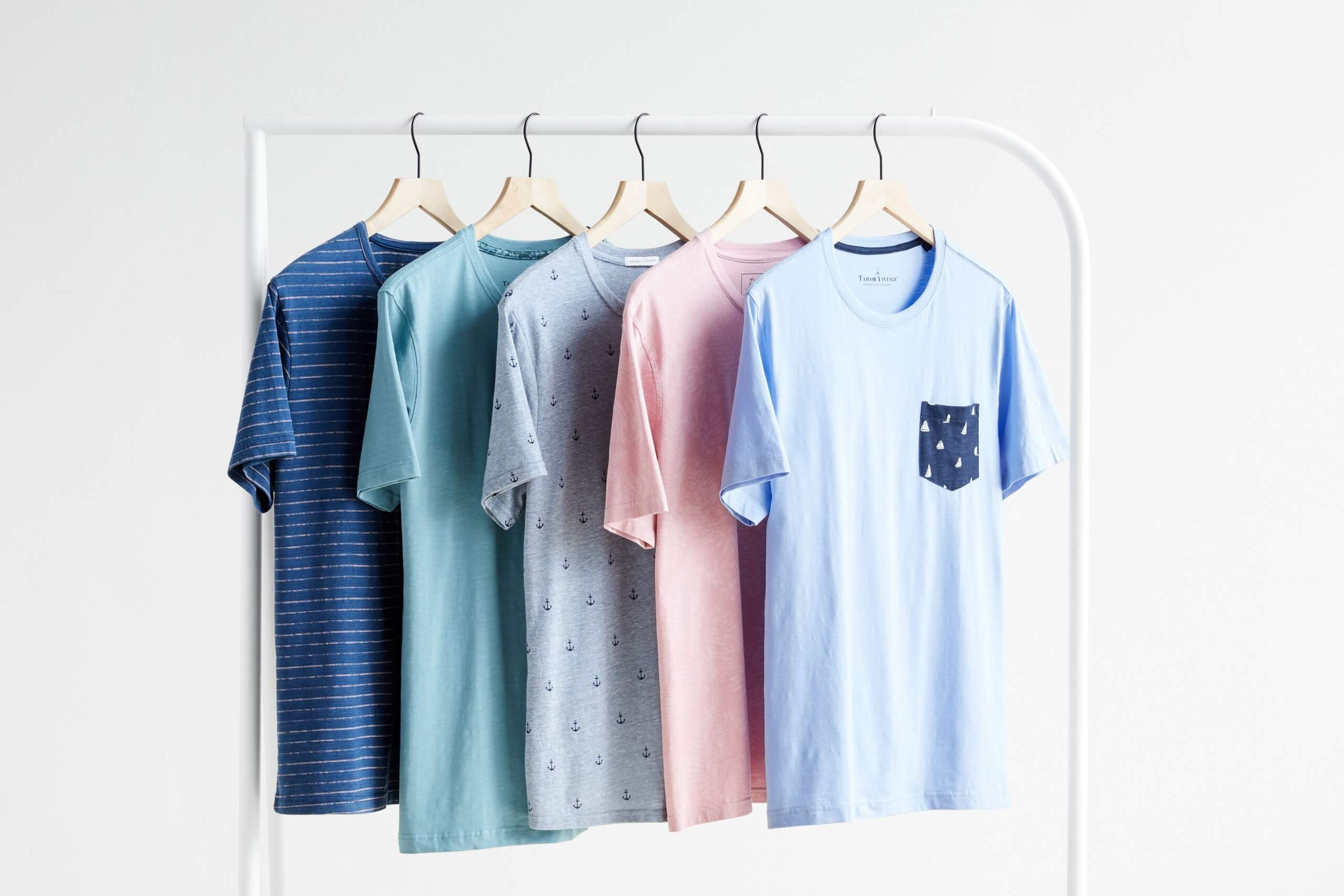 Stitch Fix Men's baby blue crew neck t-shirt, pink crew neck t-shirt, baby blue anchor print crew neck t-shirt, teal crew neck t-shirt and blue striped crew neck t-shirt hanging on white rack.
