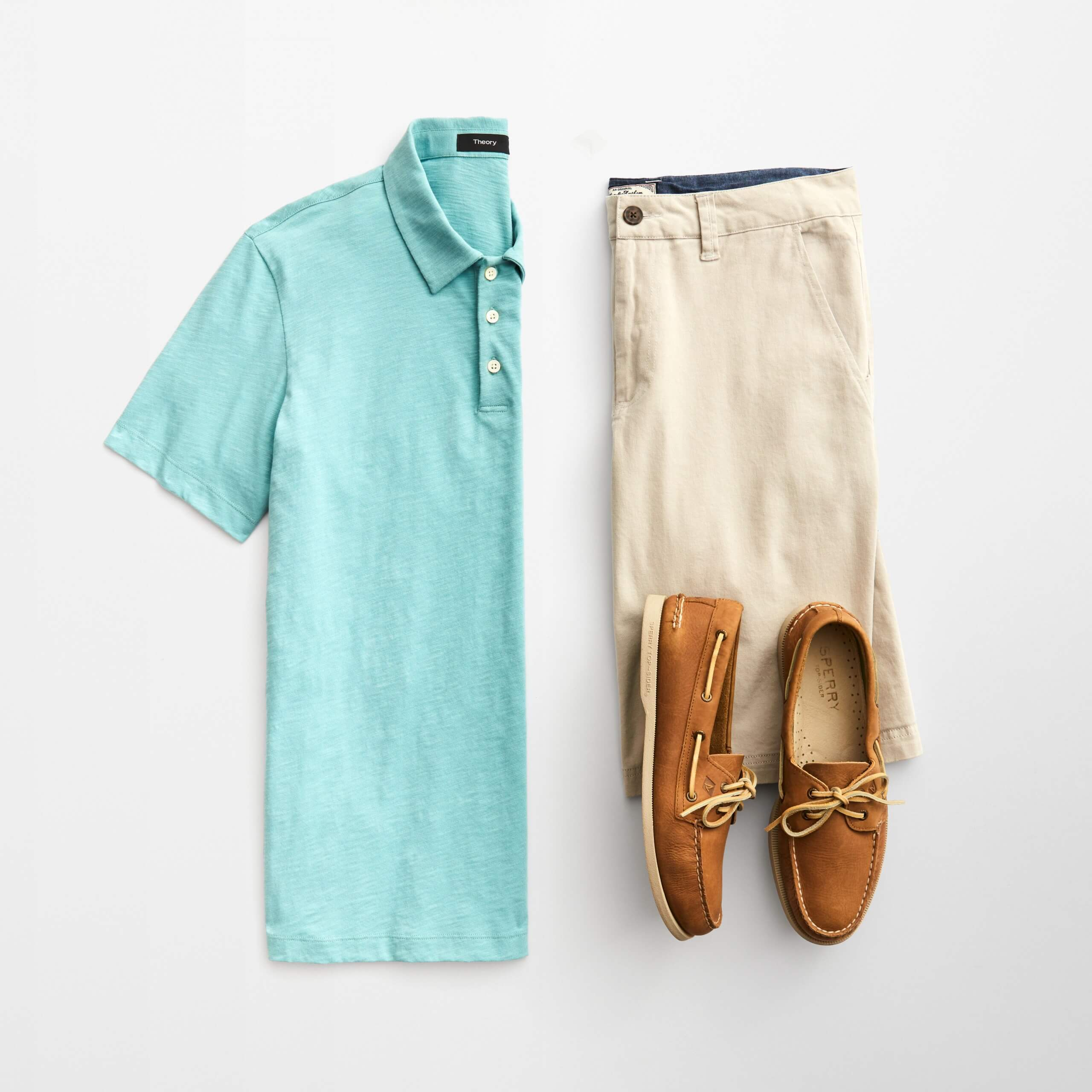 Stitch Fix Men's outfit laydown featuring a light blue polo, khaki shorts and brown boat shoes.