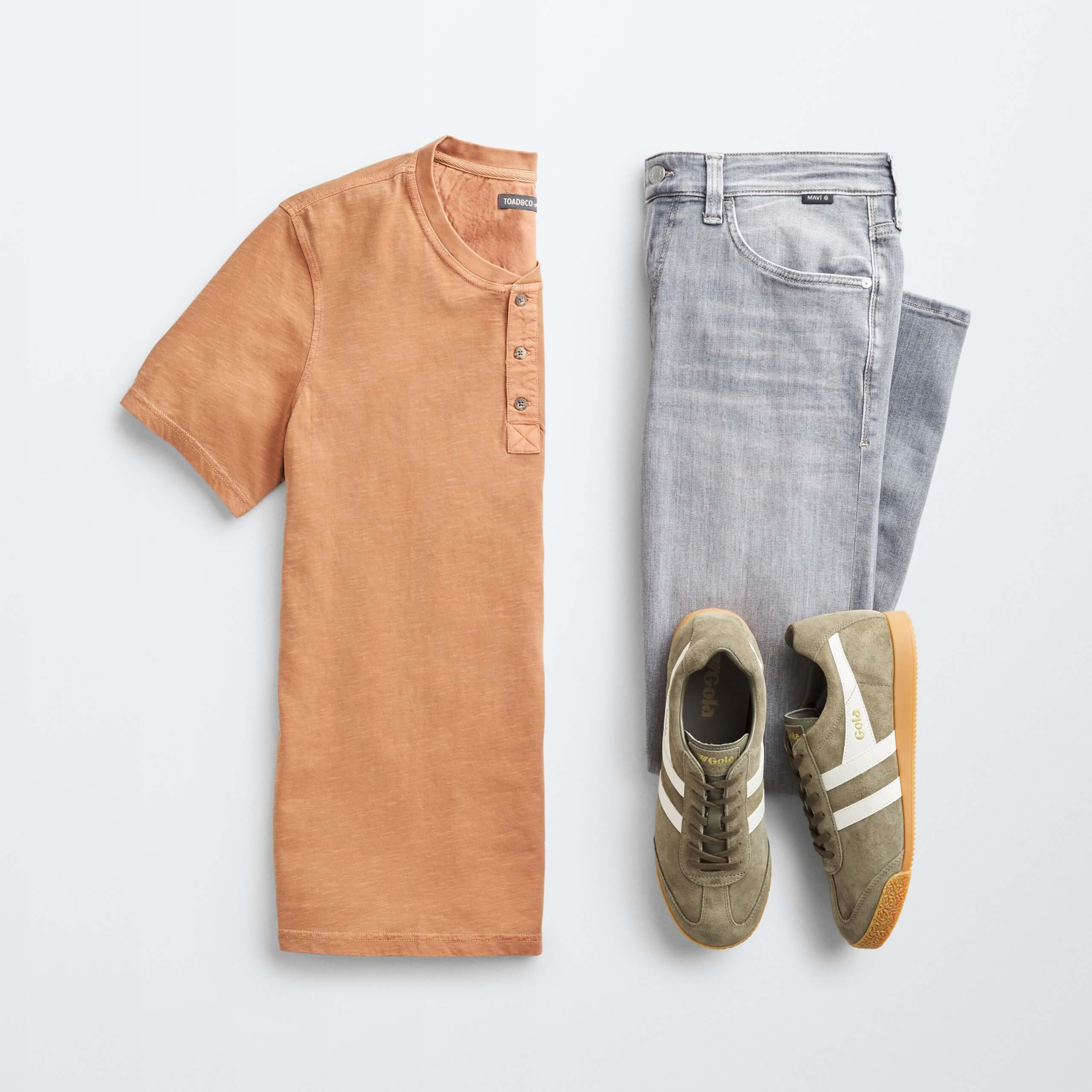 Stitch Fix Men's outfit laydown featuring orange henley shirt, grey jeans and olive green sneakers.