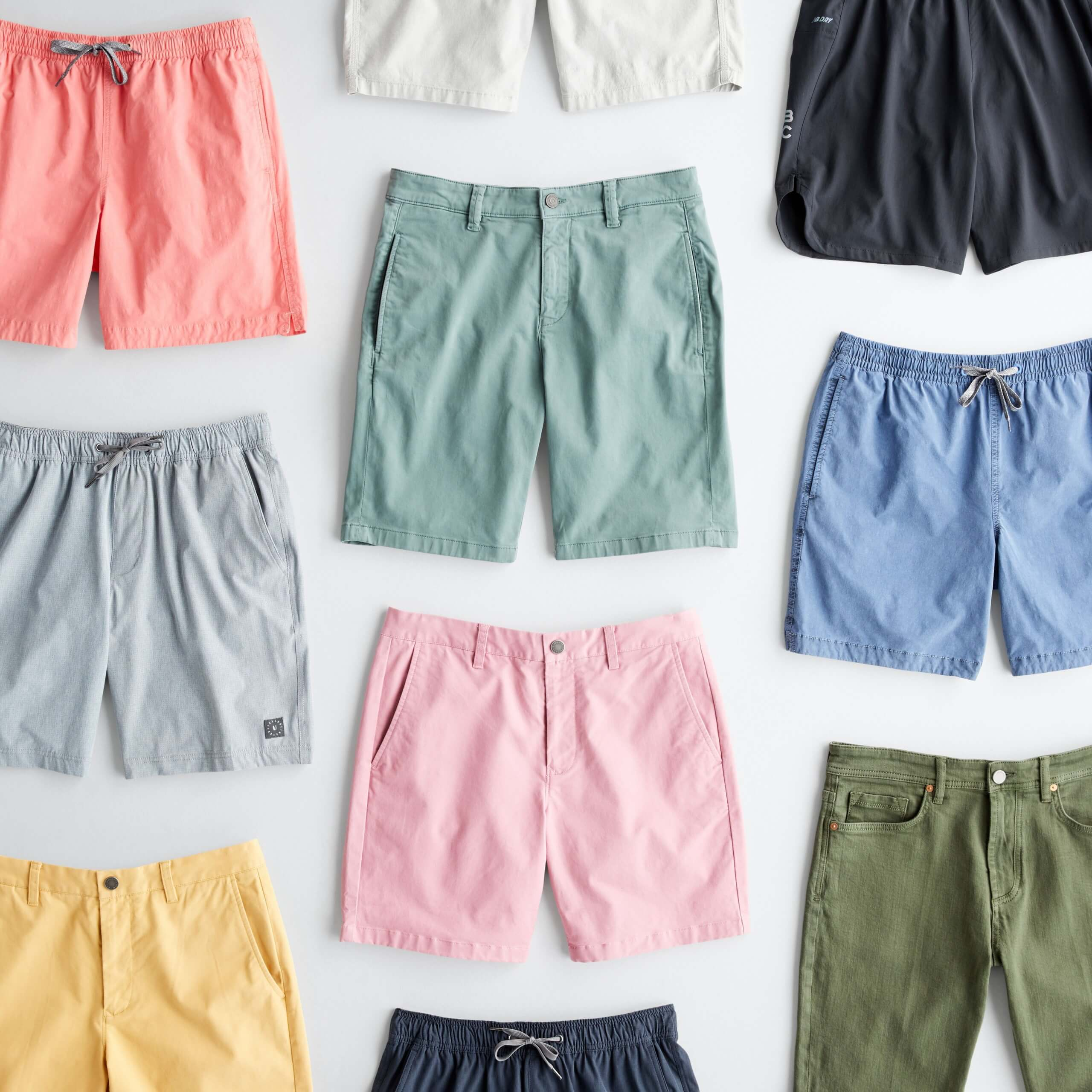 Stitch Fix Men's outfit laydown featuring multiple pairs of shorts in coral, white, green, black, blue, pink, yellow and grey.
