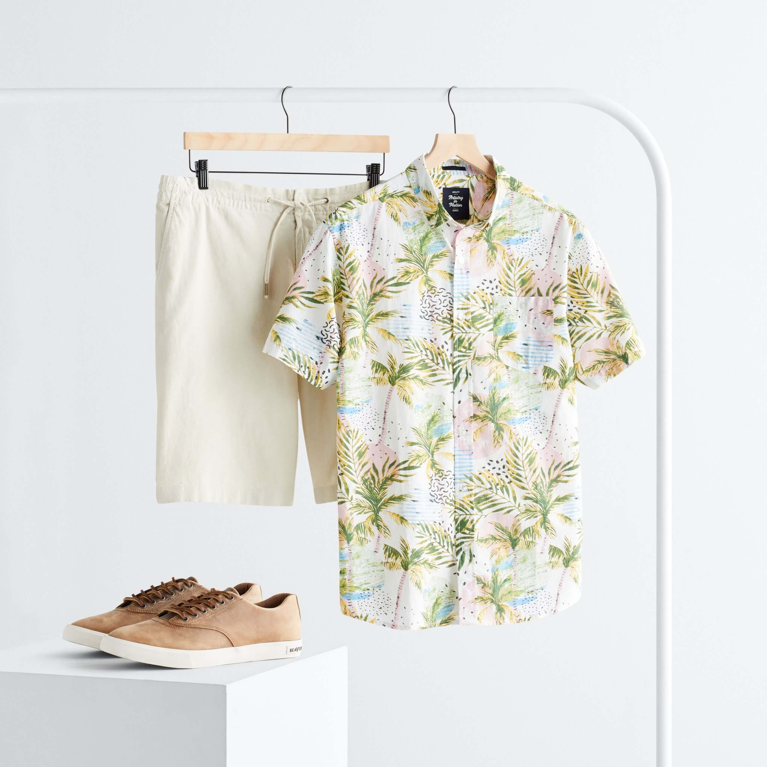 Stitch Fix Men's rack image with white, green and pink tropical print button-down short sleeve shirt and cream shorts hanging on white rack next to brown leather sneakers on white block.