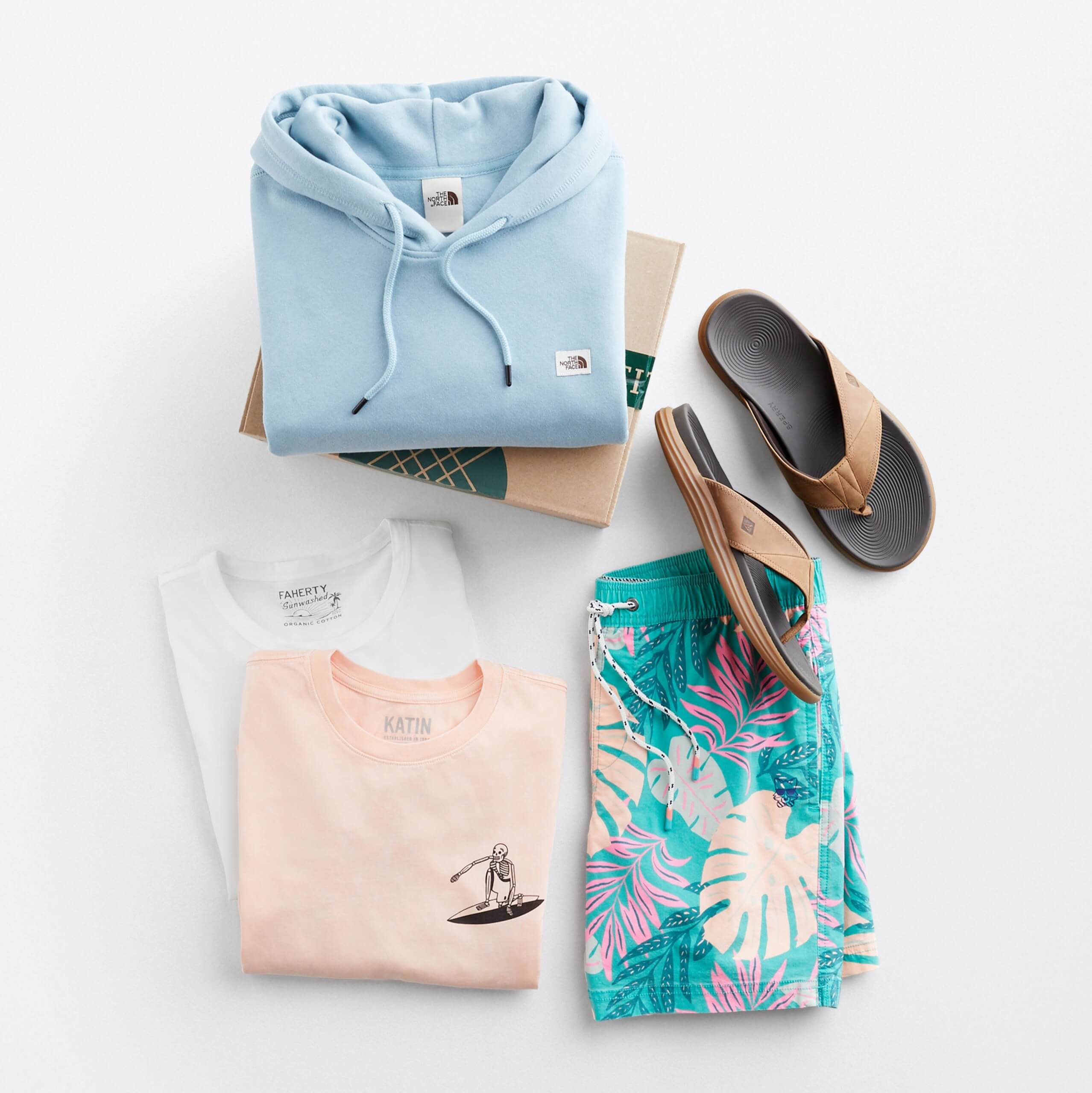 Stitch Fix Men's outfit laydown featuring a light blue hoodie on a Stitch Fix delivery box, next to tan flip flop sandals, tropical print shorts and two crew neck t-shirts in pink and white.