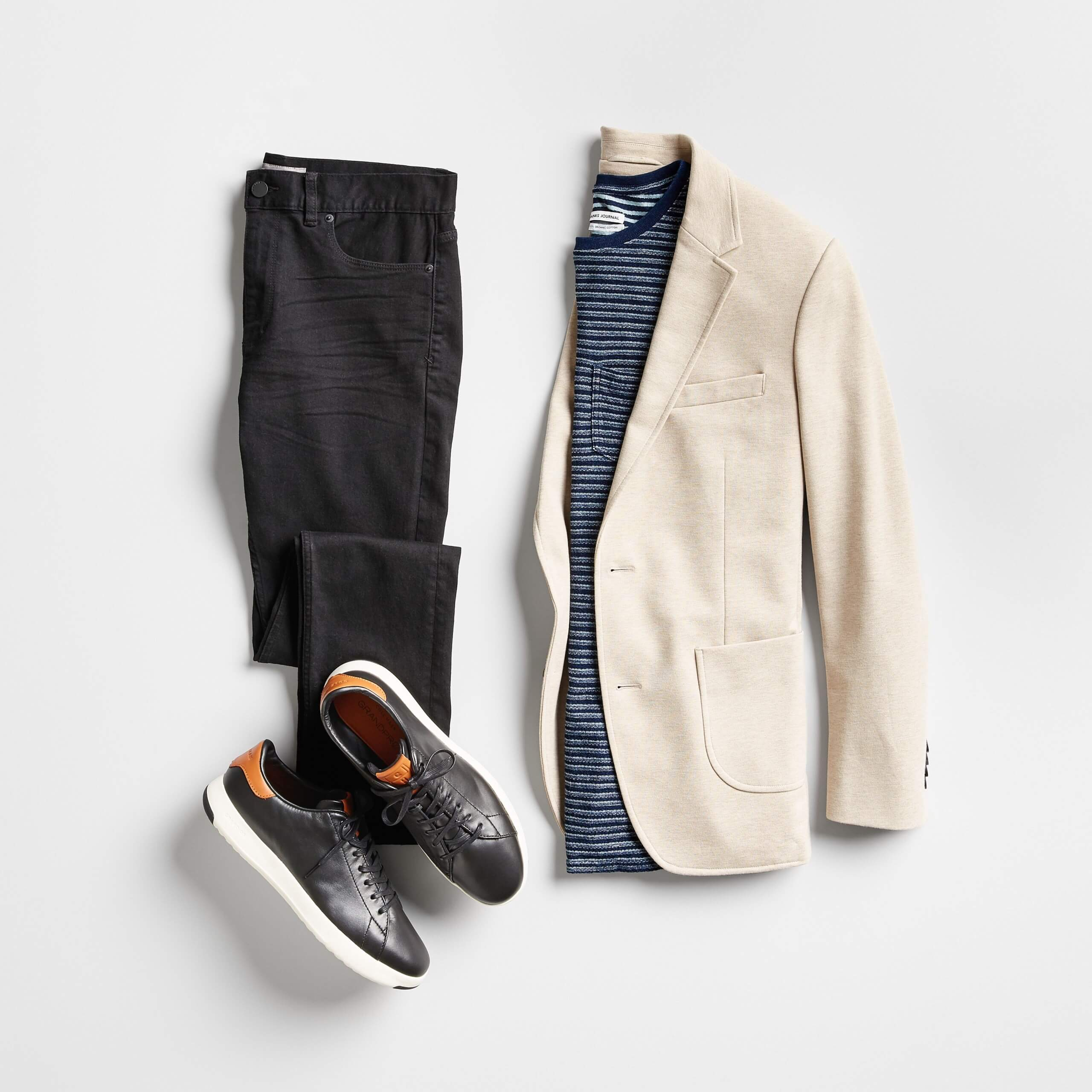 Stitch Fix Men's outfit laydown featuring a beige blazer over a navy striped tee, next to black skinny jeans and black leather sneakers.