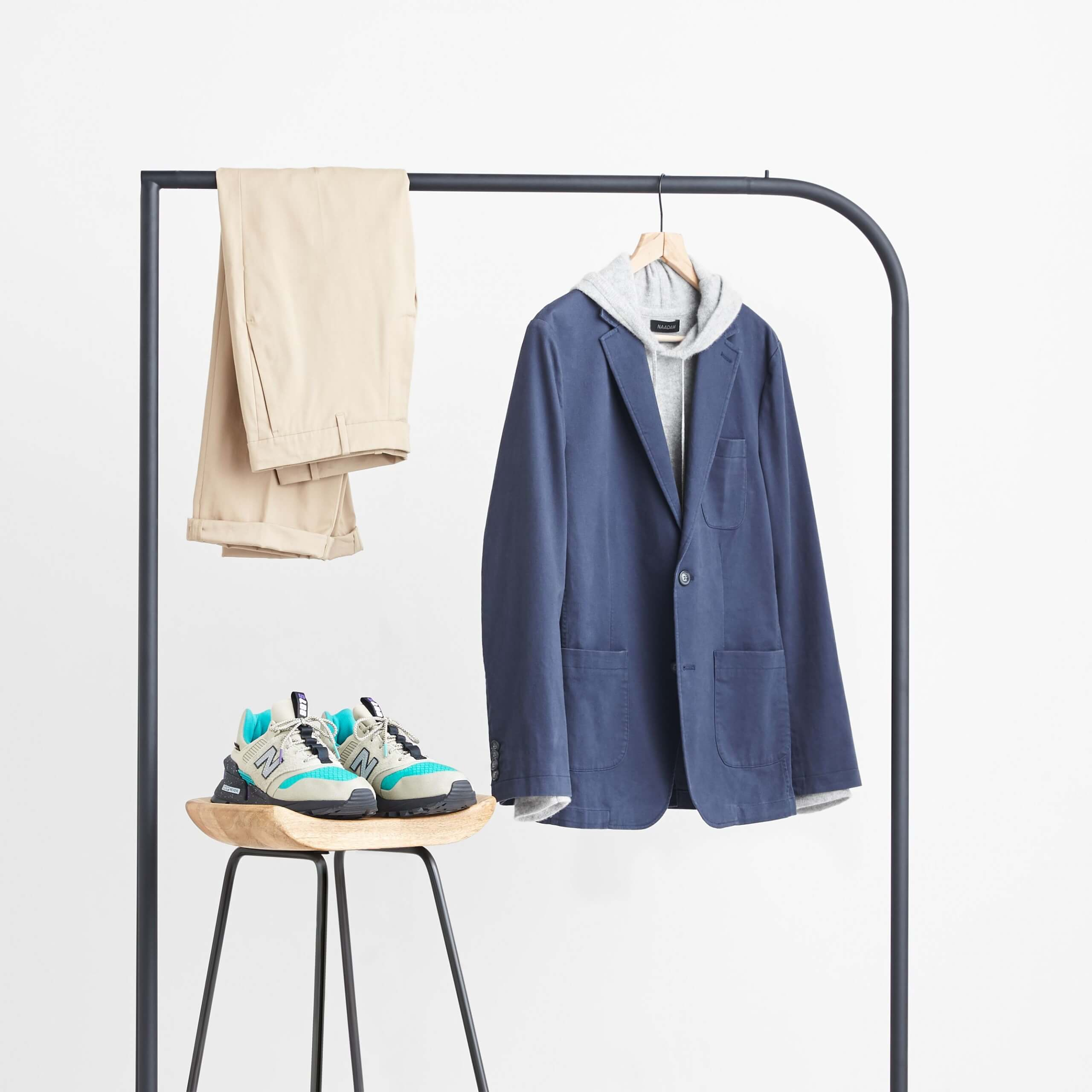 Stitch Fix Men's navy blazer, grey hoodie and tan chinos hanging on a black rack next to tan nylon sneakers sitting on a wooden stool.
