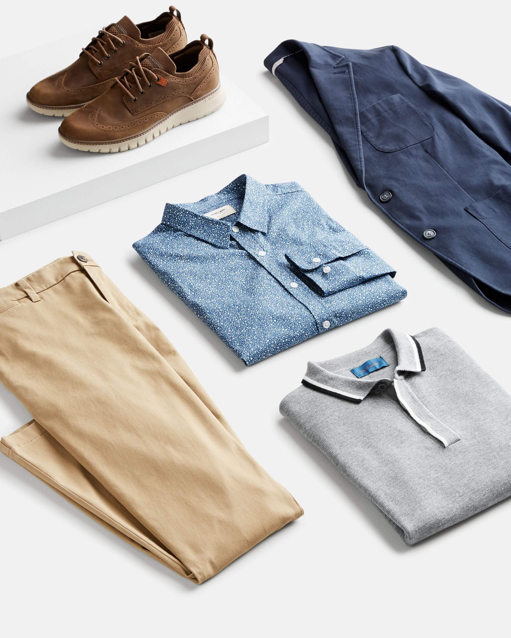 Stitch Fix Men's outfit laydown featuring khaki pants, grey polo, chambray button-up, navy blazer and brown oxford shoes.