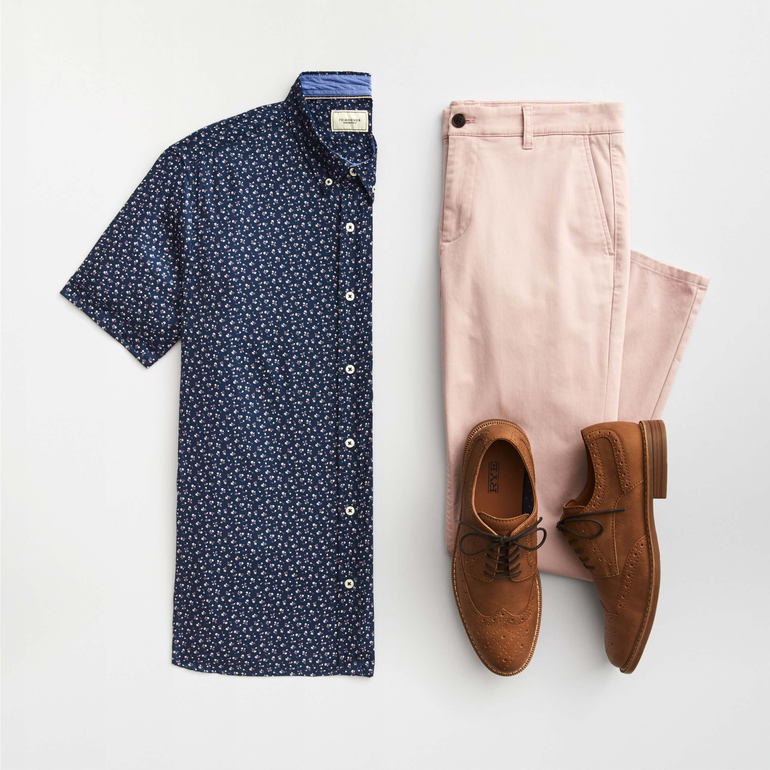 Stitch Fix Men's outfit laydown featuring short-sleeved navy button-down with small floral print, pink chinos and brown brogues.