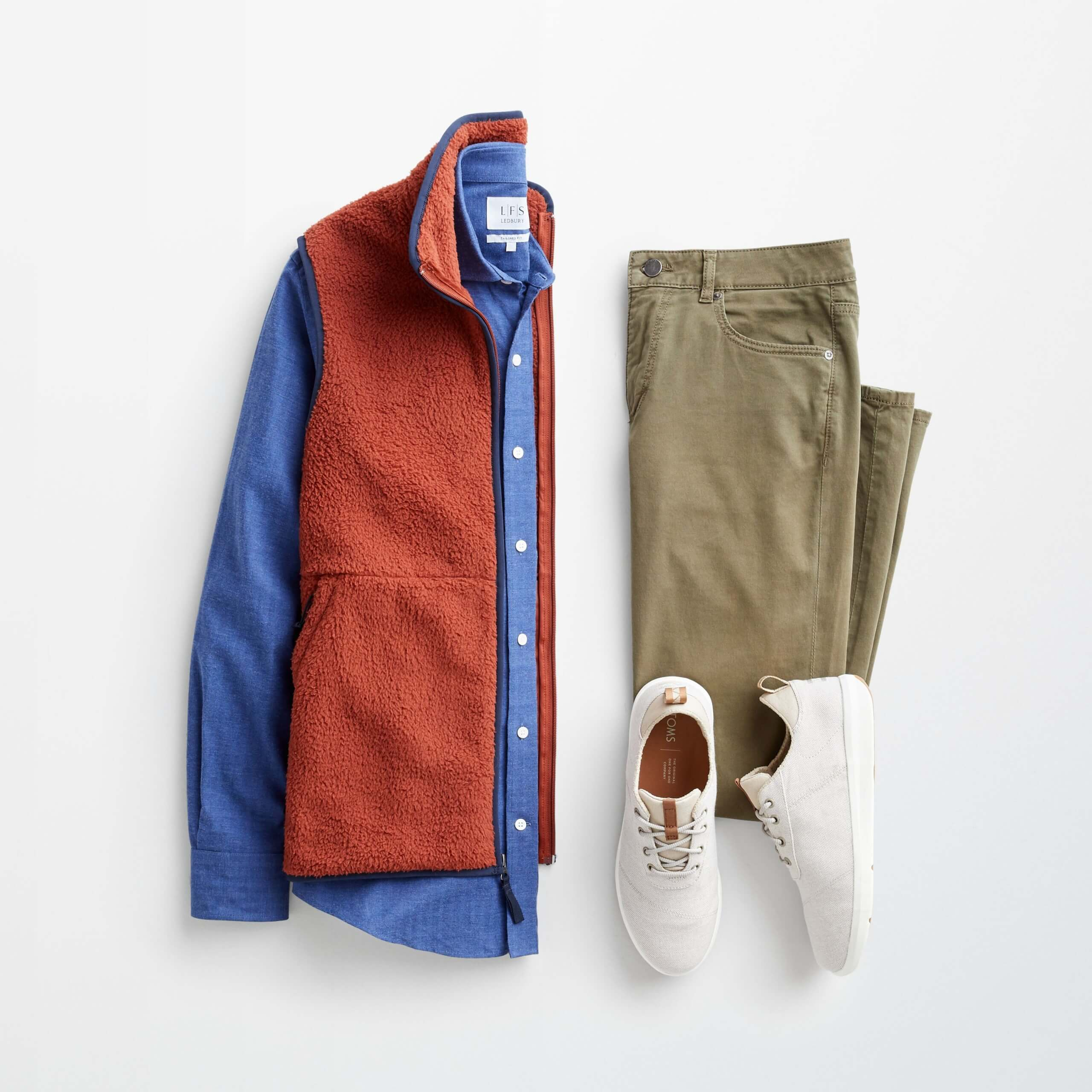 Stitch Fix Men's outfit laydown featuring an orange vest over a blue long sleeve button-down shirt, olive green jeans and cream lace-up sneakers.