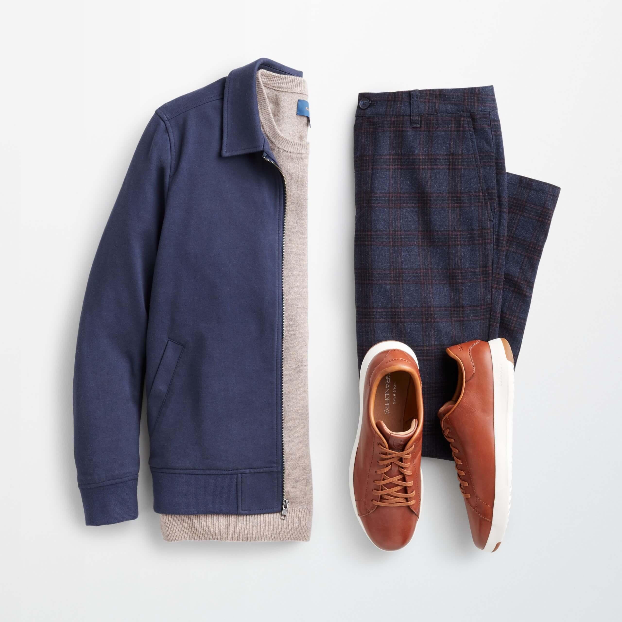 Stitch Fix Men's outfit laydown featuring navy harrington jacket over cream pullover sweater next to navy plaid chinos and brown leather sneakers.