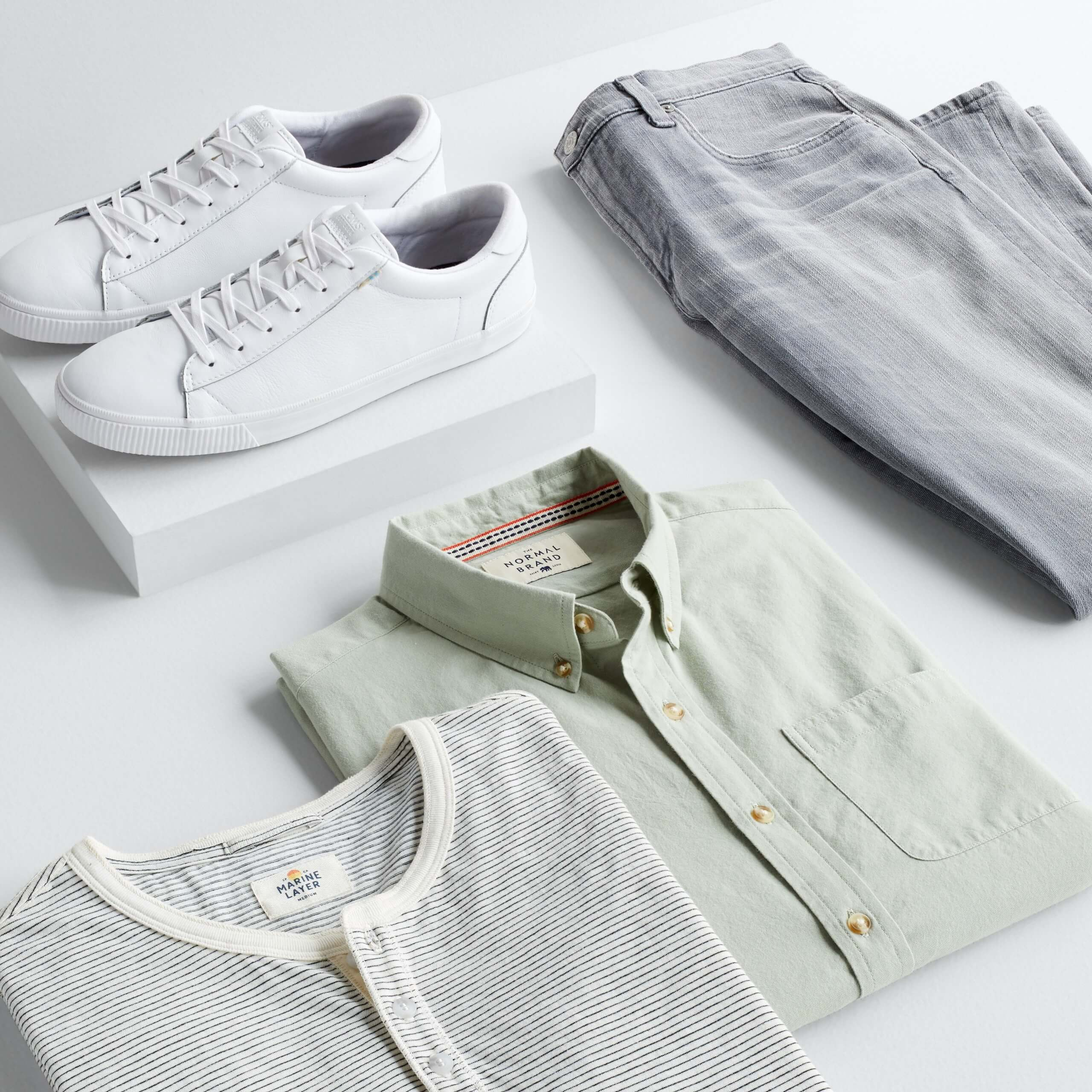 Stitch Fix Men's outfit laydown featuring white and grey striped henley shirt, sage green long sleeve button-down shirt and grey jeans next to white sneakers on a white block.