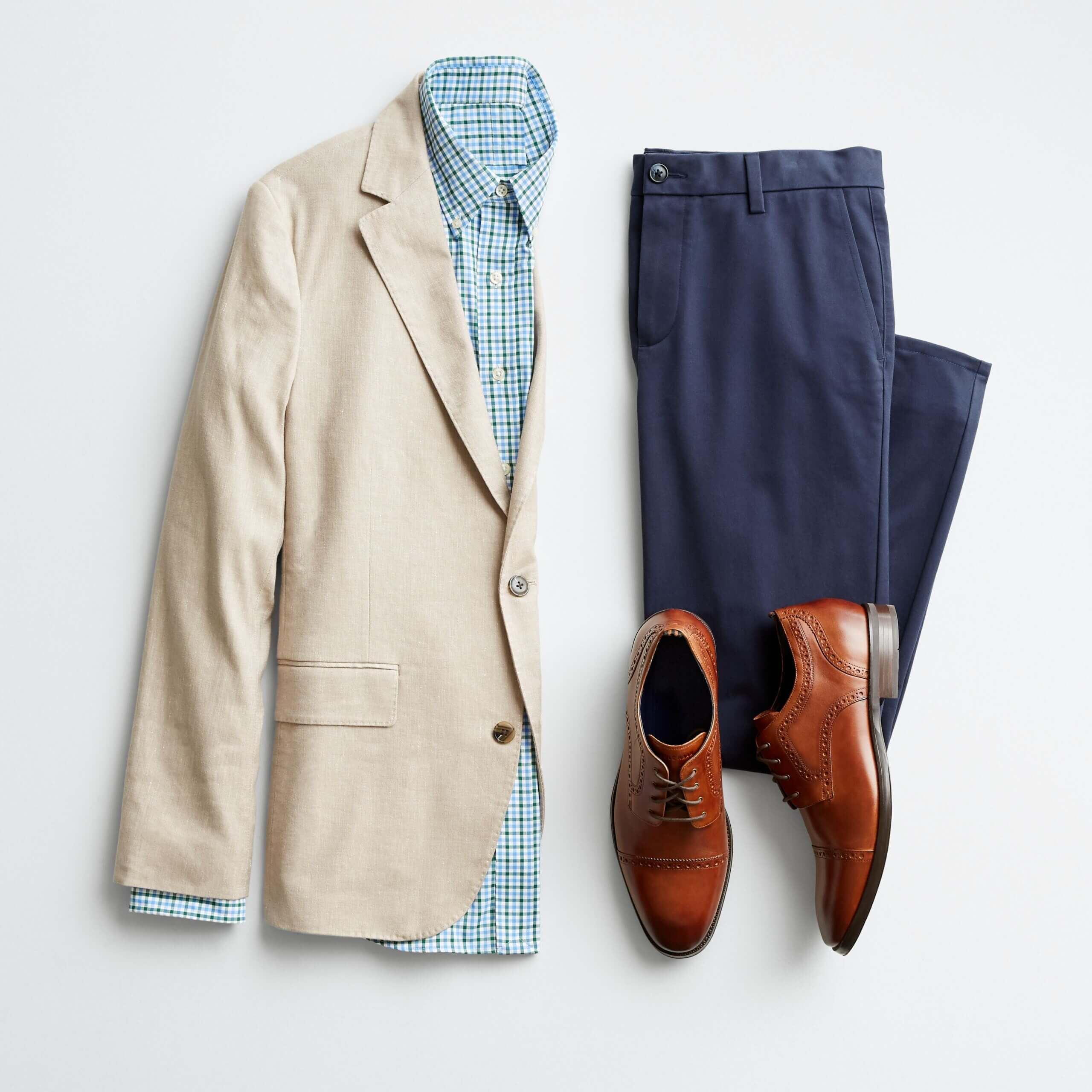 Stitch Fix men's outfit laydown featuring navy trousers, blue button-up, khaki blazer and cognac shoes.