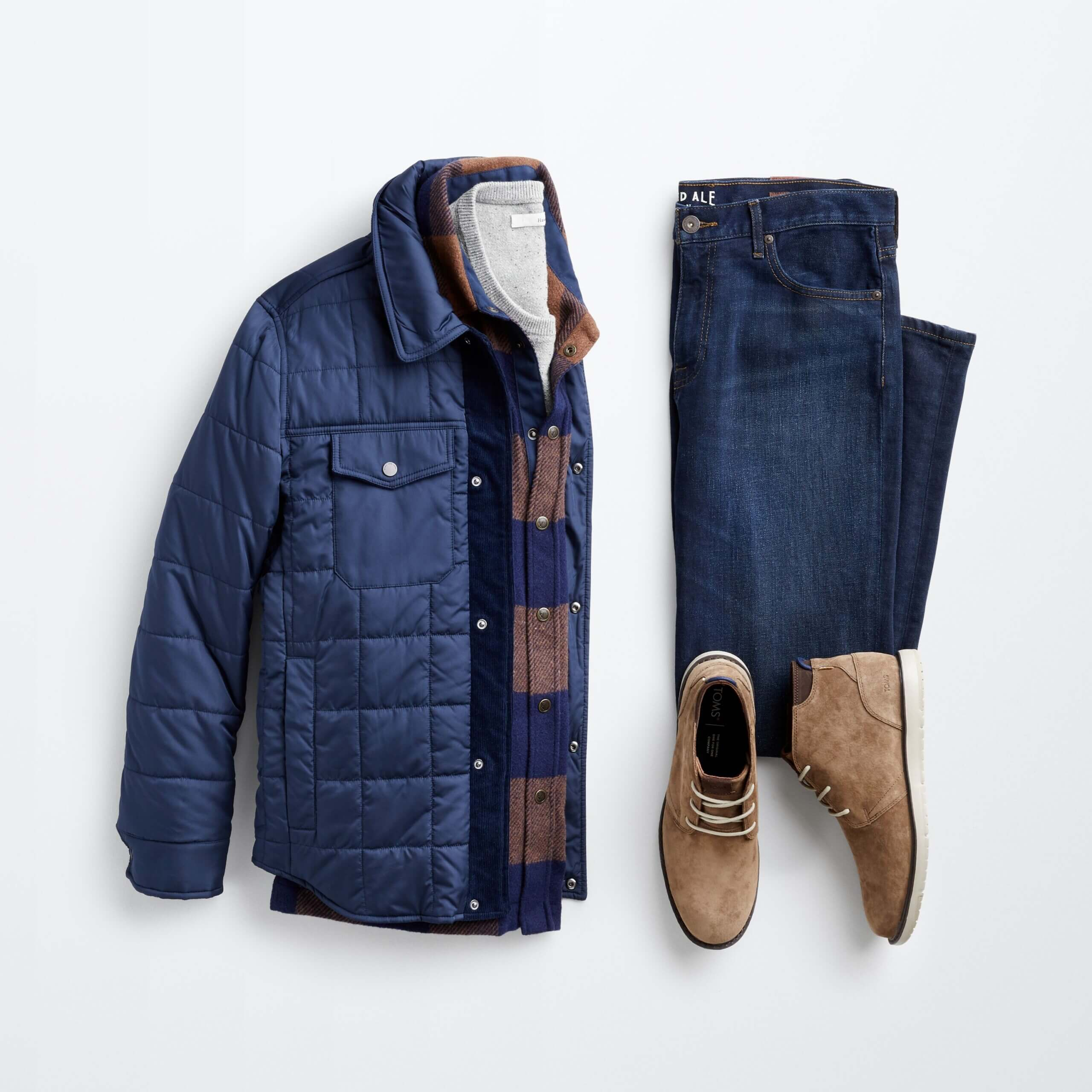 Stitch Fix men's outfit laydown featuring blue denim, grey t-shirt, plaid flannel button-up, navy puffer jacket and brown chukkas.