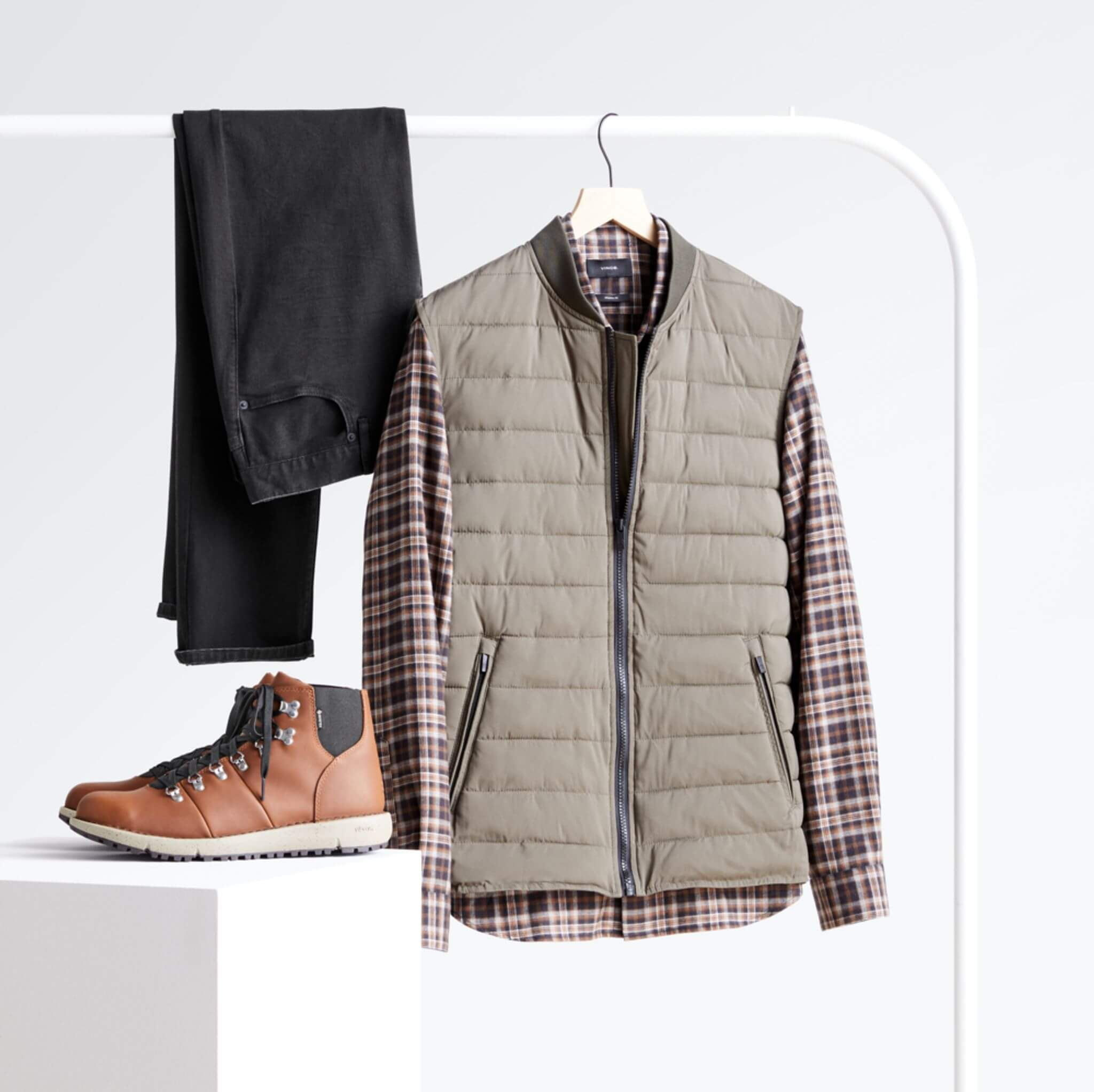 Stitch Fix Men's black slim-fit jeans, long-sleeved woven plaid button-down shirt and bomber vest hanging on a white rack with brown leather boots on a white podium.