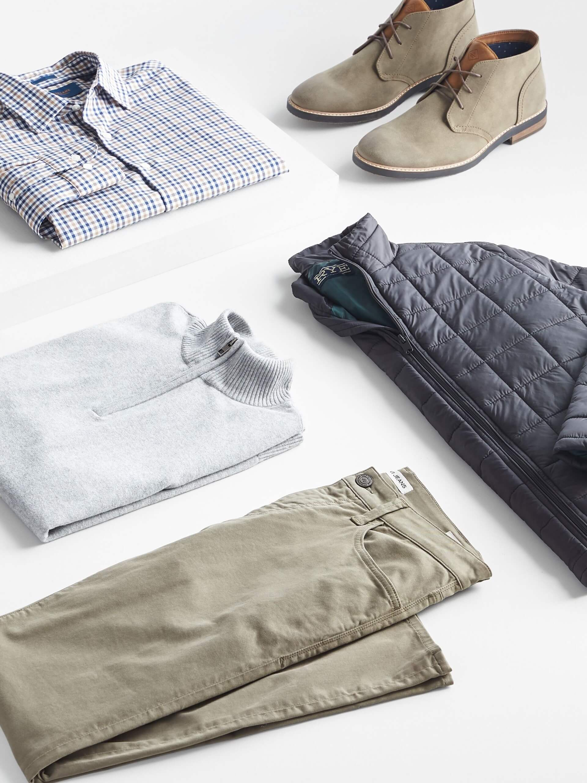 Stitch Fix Men's outfit laydown featuring white and blue button-down shirt, beige chukkas, grey quarter-zip pullover, olive-green pants, and black puffer jacket.