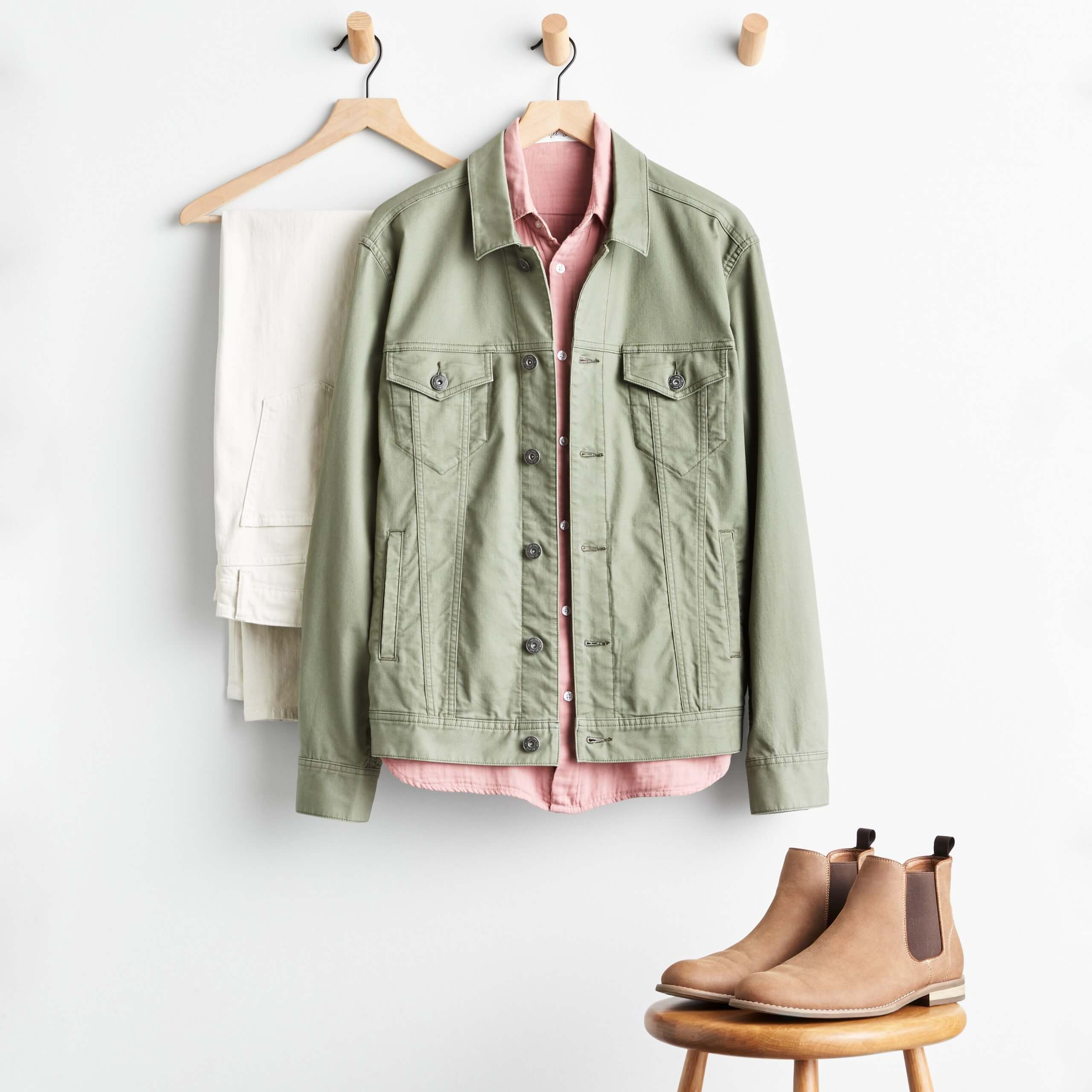 Stitch Fix Men's khaki pants hanging on wooden hanger, olive denim jacket over pink woven shirt on wooden hanger and tan chelsea boots on a wooden stool.