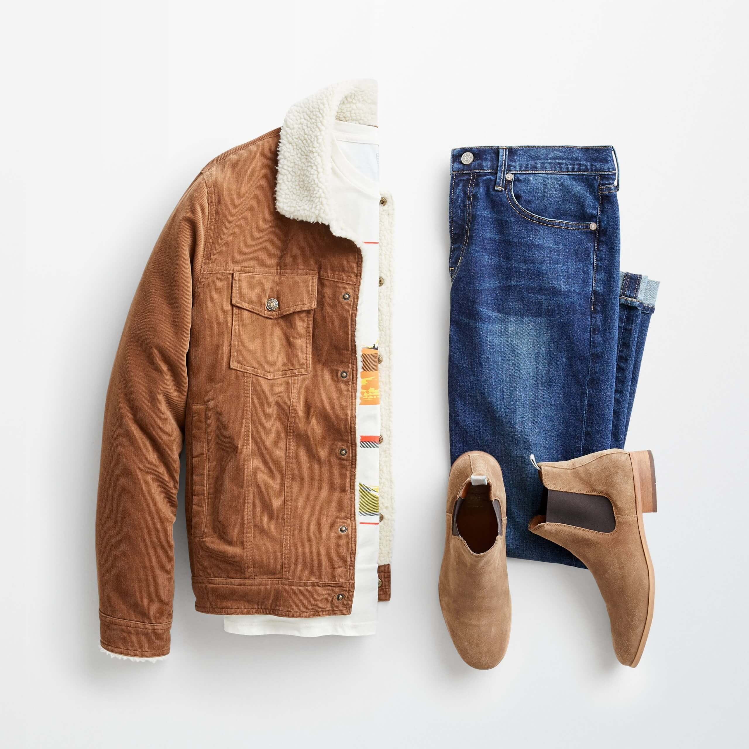 Stitch Fix Men's outfit laydown featuring a brown corduroy jacket with sherpa lining over a graphic t-shirt, next to folded blue jeans and brown chelsea boots.