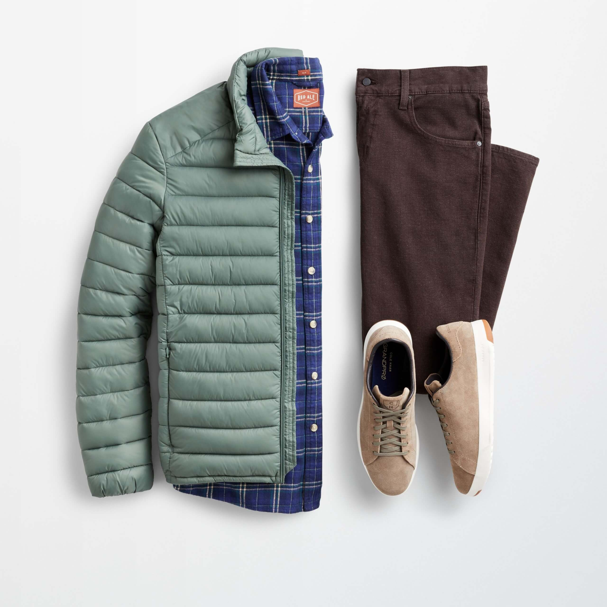 Stitch Fix Men's outfit laydown featuring green puffer jacket over navy plaid button-down shirt, brown pants and tan suede sneakers.