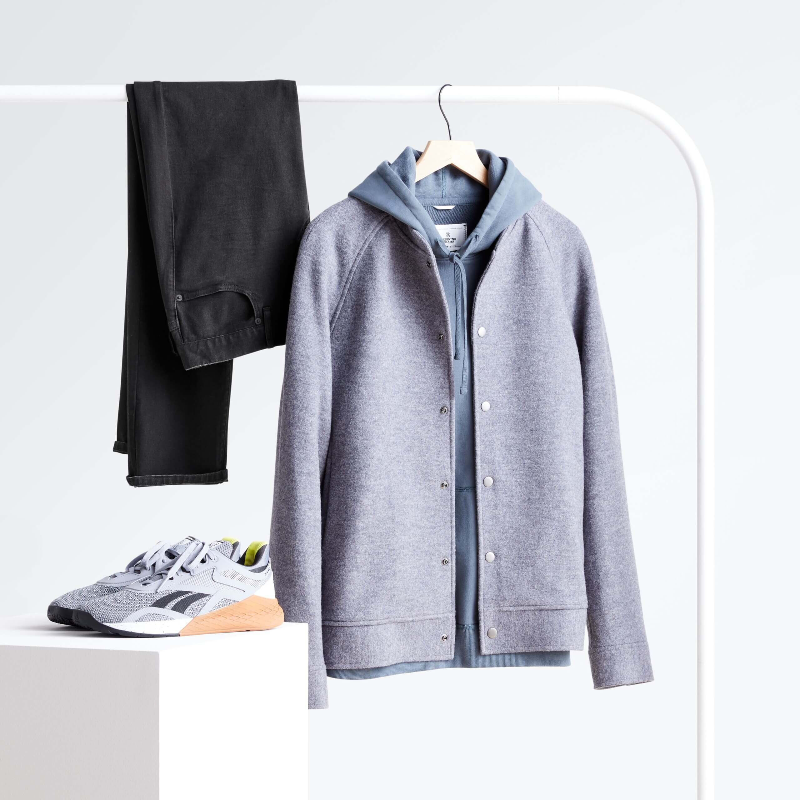 Stitch Fix men's rack image featuring grey wool bomber over blue hoodie and black jeans hanging on white rack next to gray active sneakers on white block.