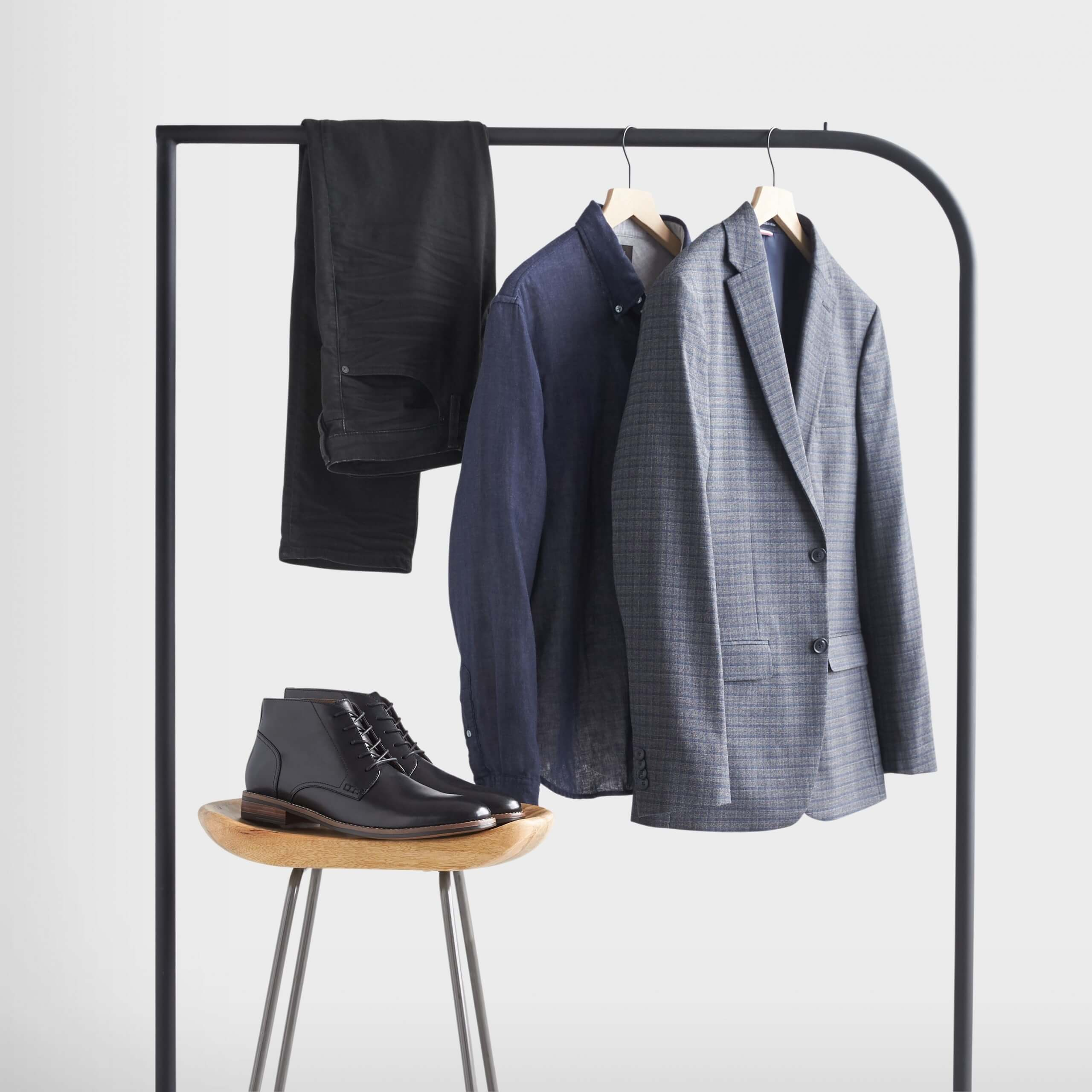 Stitch Fix Men's rack image featuring blue blazer, navy blue dress shirt and black jeans hanging on black rack, next to black leather chukkas on wooden stool.