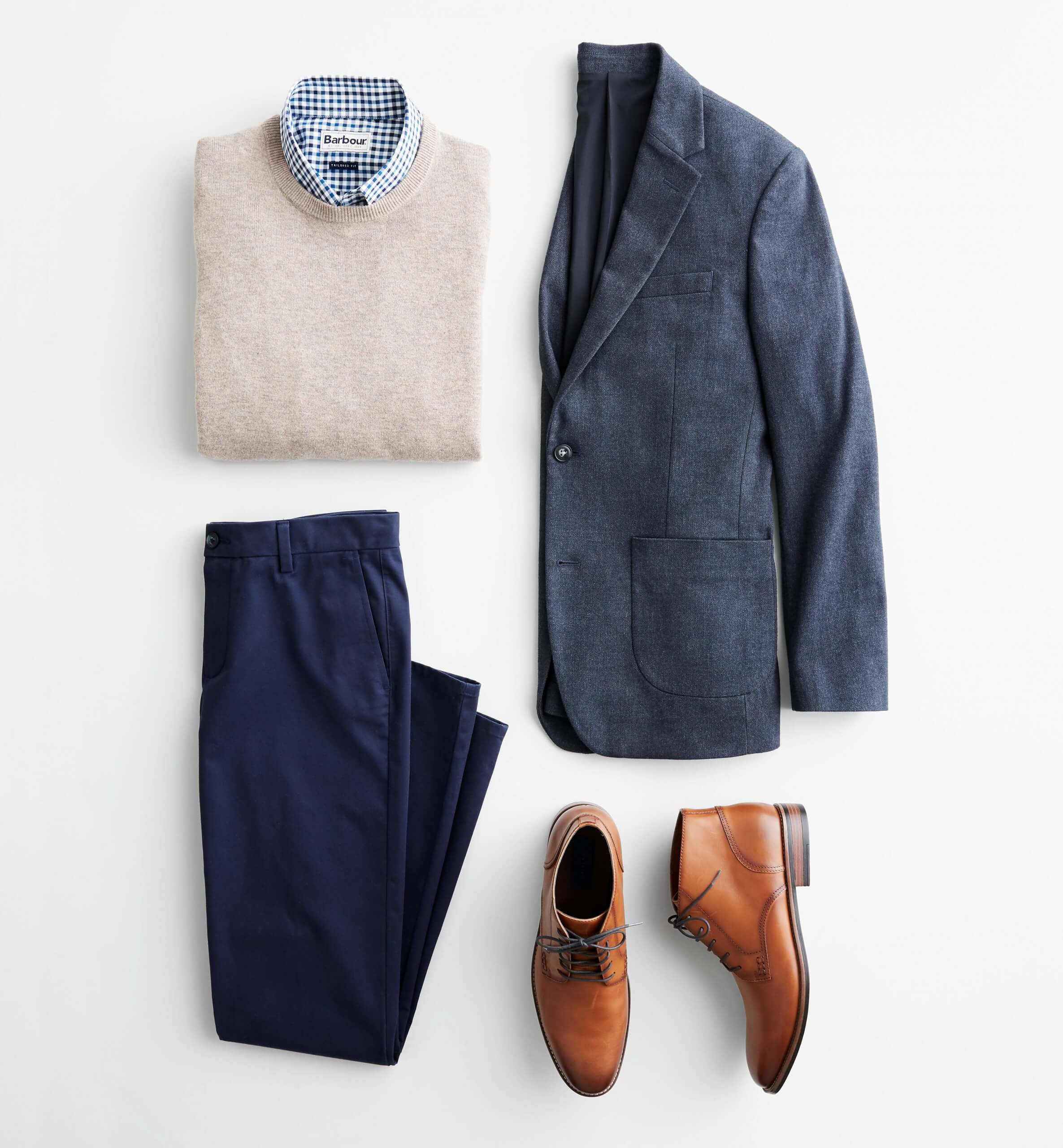 Stitch Fix Men's outfit laydown featuring navy blazer, cream crewneck sweater over blue collared shirt, navy trousers and brown leather chukkas.