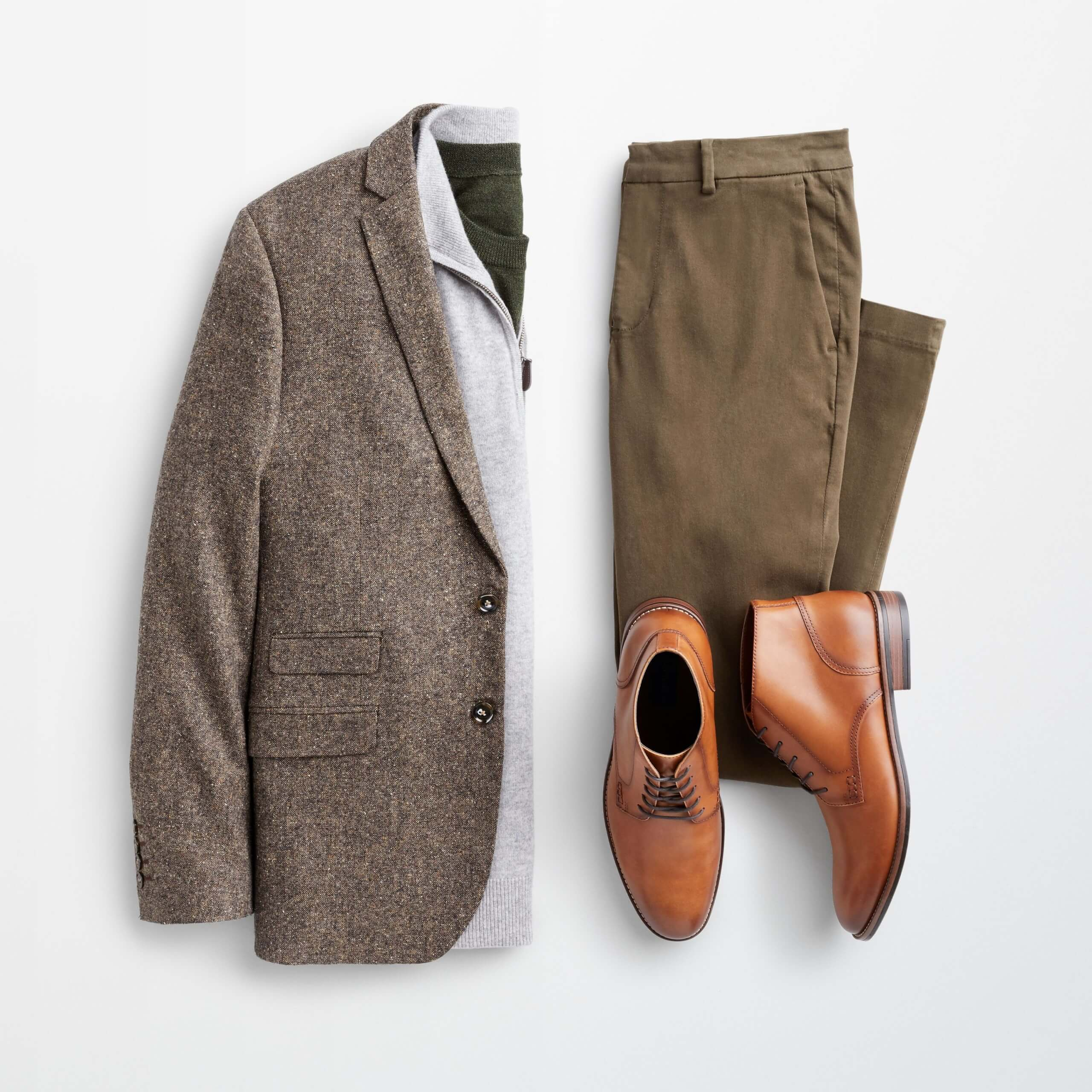 Stitch Fix Men's outfit laydown featuring brown blazer over grey quarter-zip wool sweater, next to olive-green trousers and brown leather chukkas.