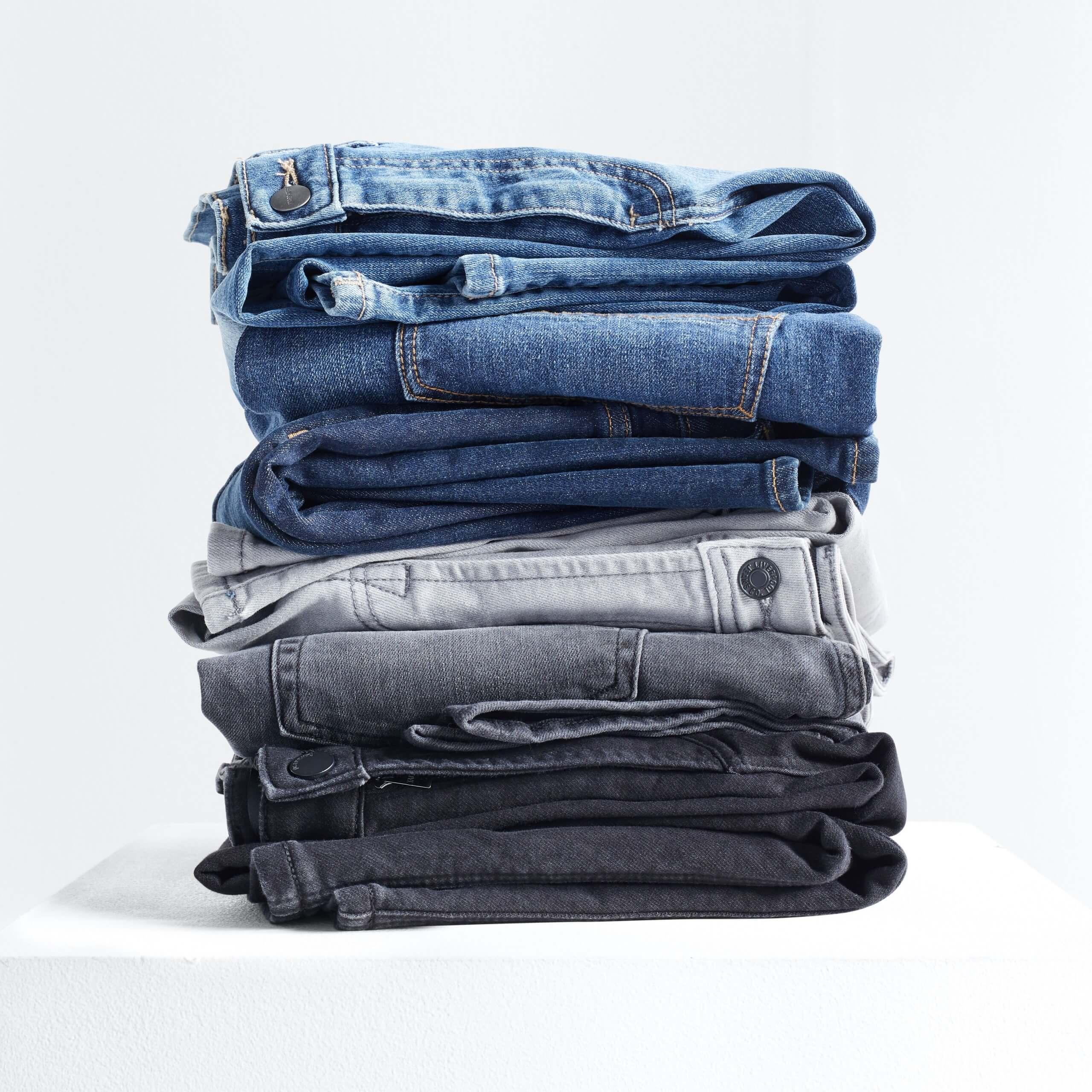 Stitch Fix Men's stack of jeans in light blue, dark blue, grey and black.