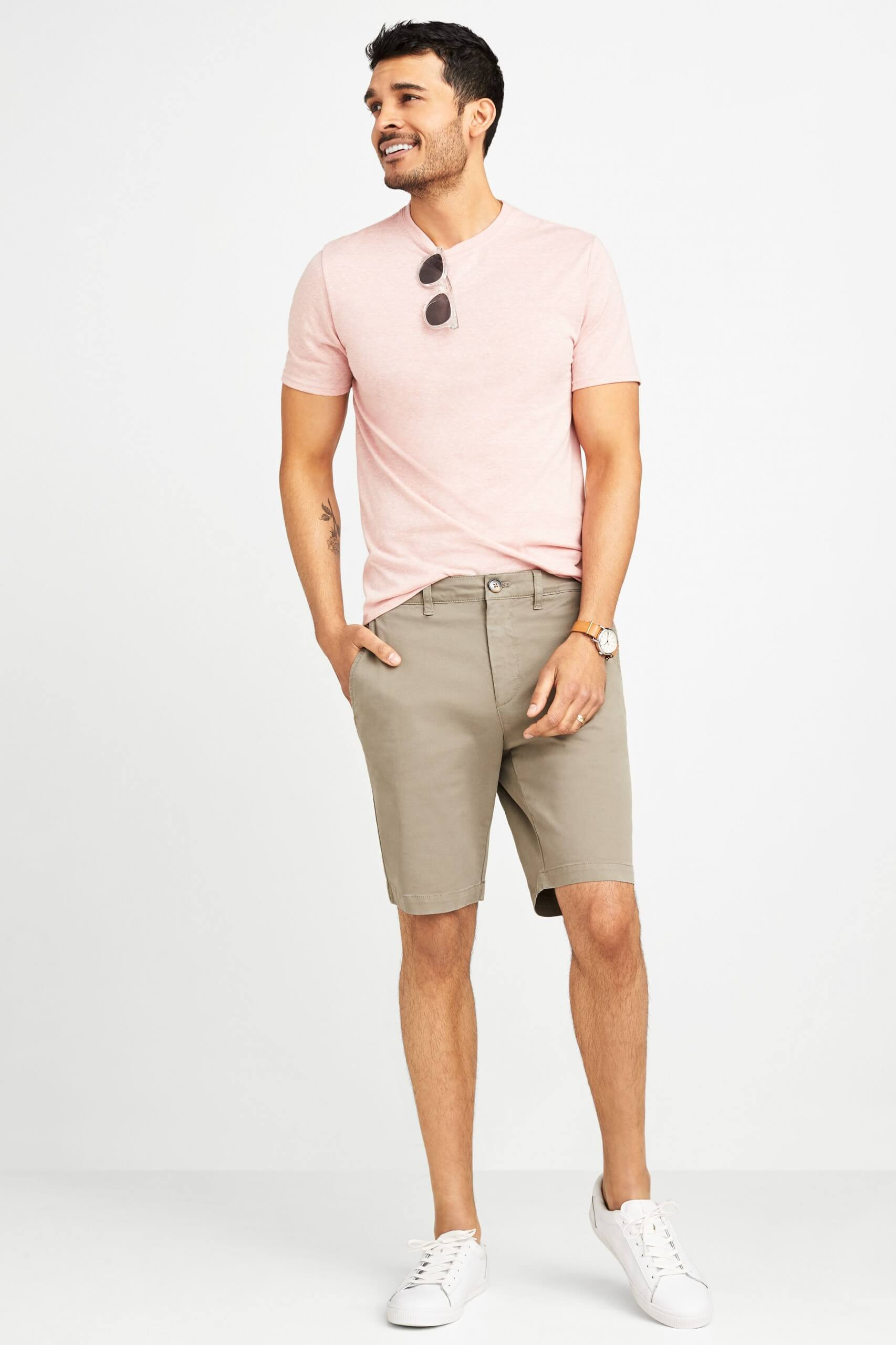 Stitch Fix Men's model wearing pink crew neck t-shirt, khaki shorts and white leather sneakers.