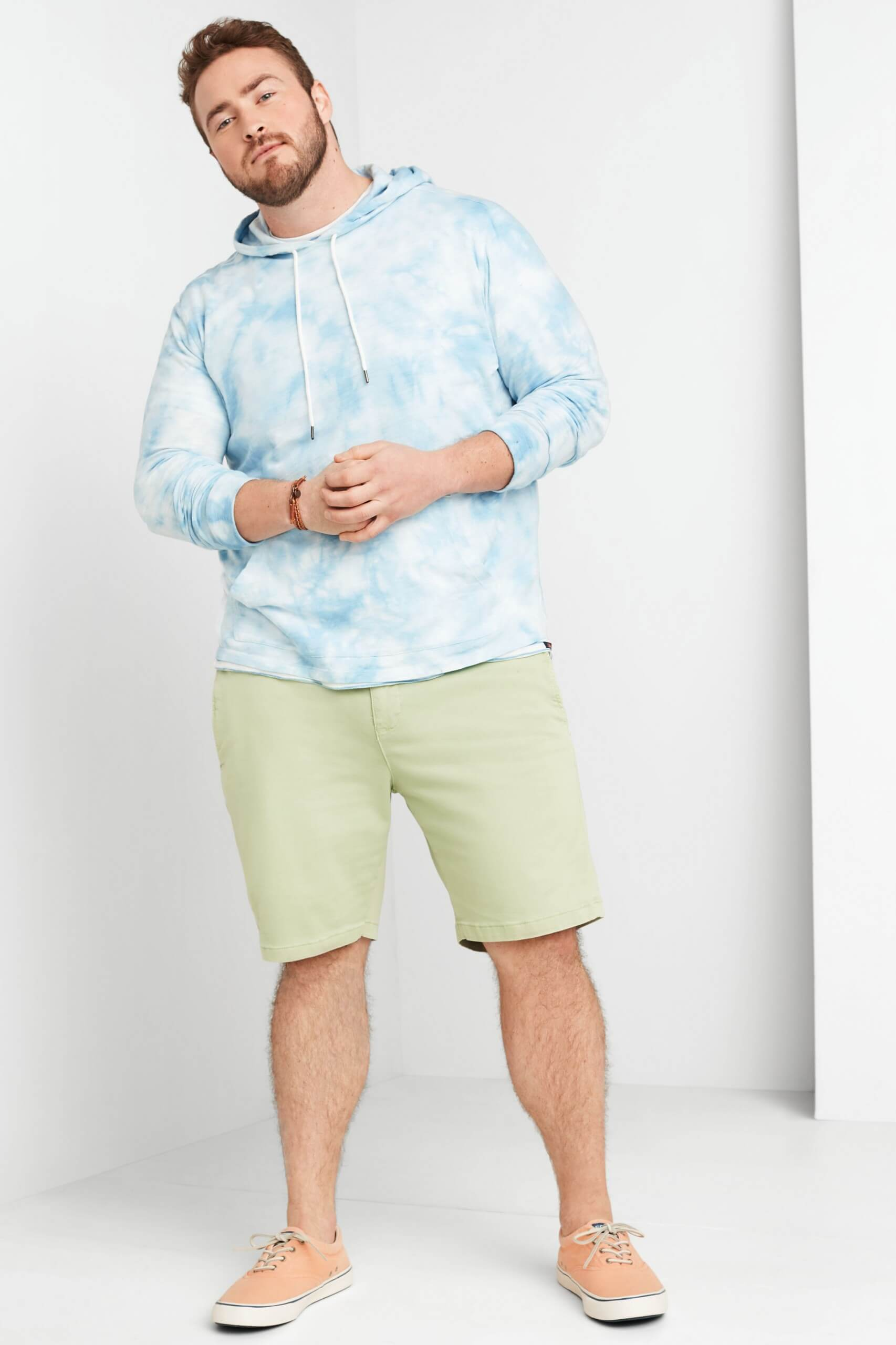 Stitch Fix Men's model wearing baby blue tie-dye hoodie, green shorts and white sneakers.