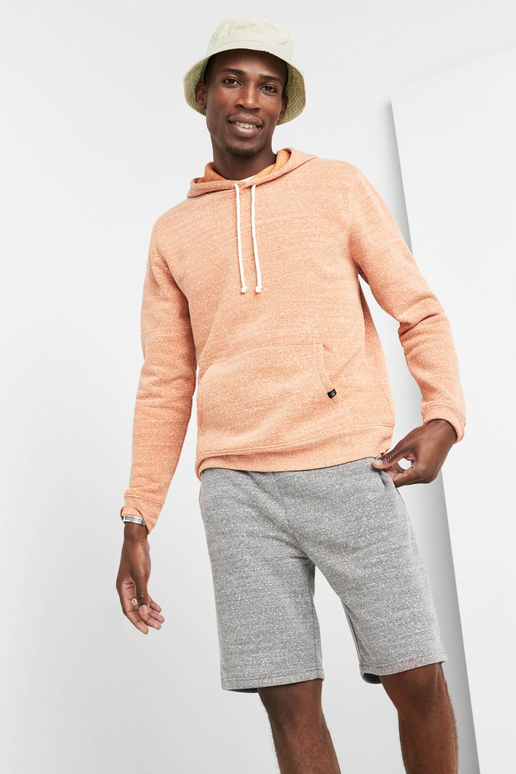 Stitch Fix Men's model wearing peach hoodie and grey shorts.