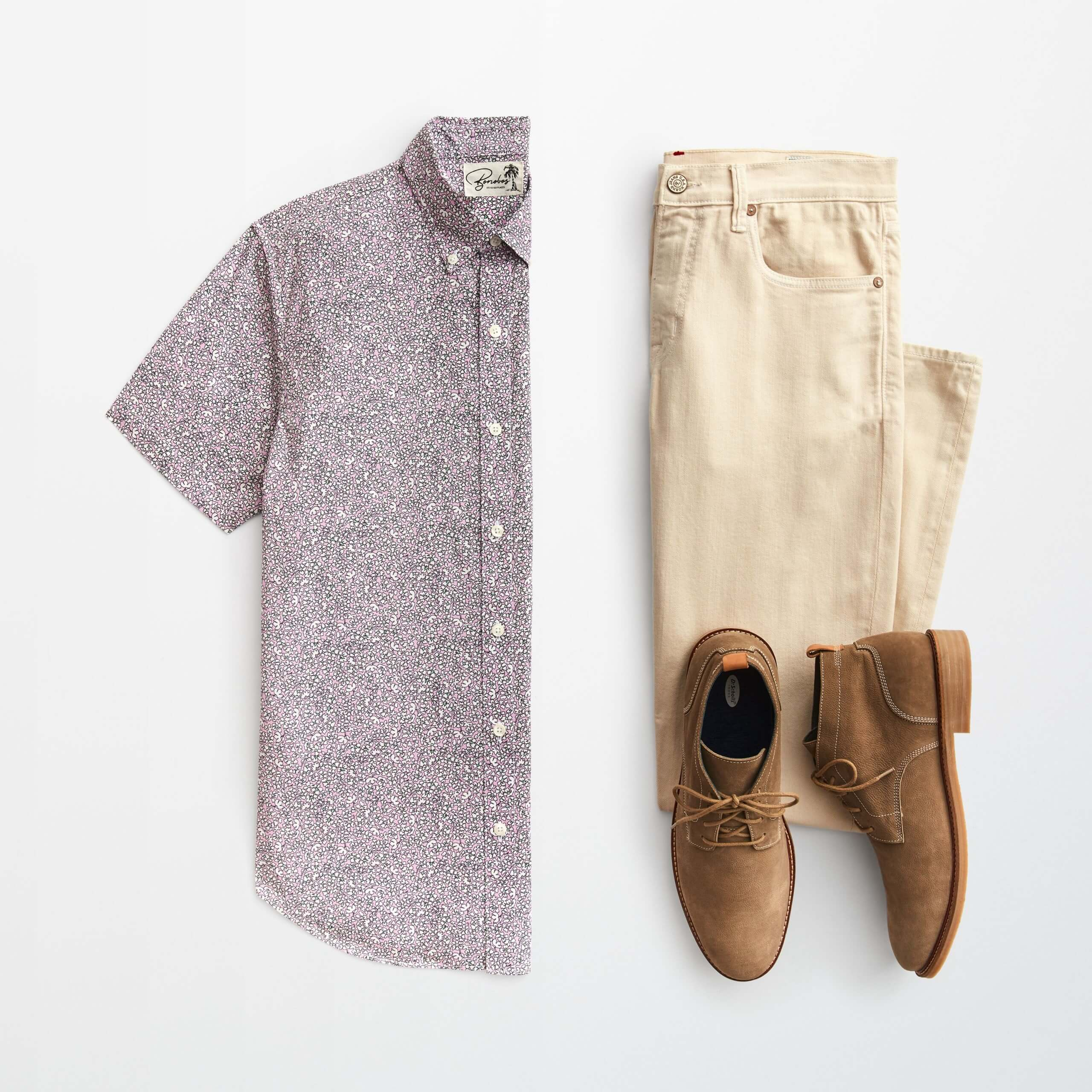Stitch Fix Men's outfit laydown patterned short-sleeved button-down shirt, khaki jeans and brown chukkas.