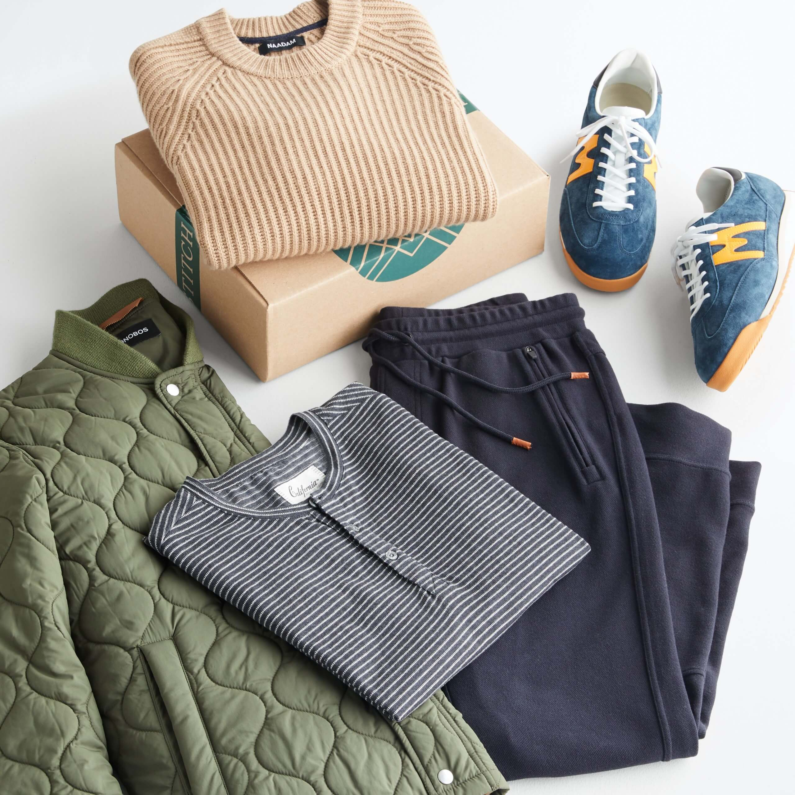 Stitch Fix Men's outfit laydown featuring camel crewneck sweater folded on Stitch Fix next to blue retro suede sneakers, blue joggers, striped henley and olive quilted bomber jacket.