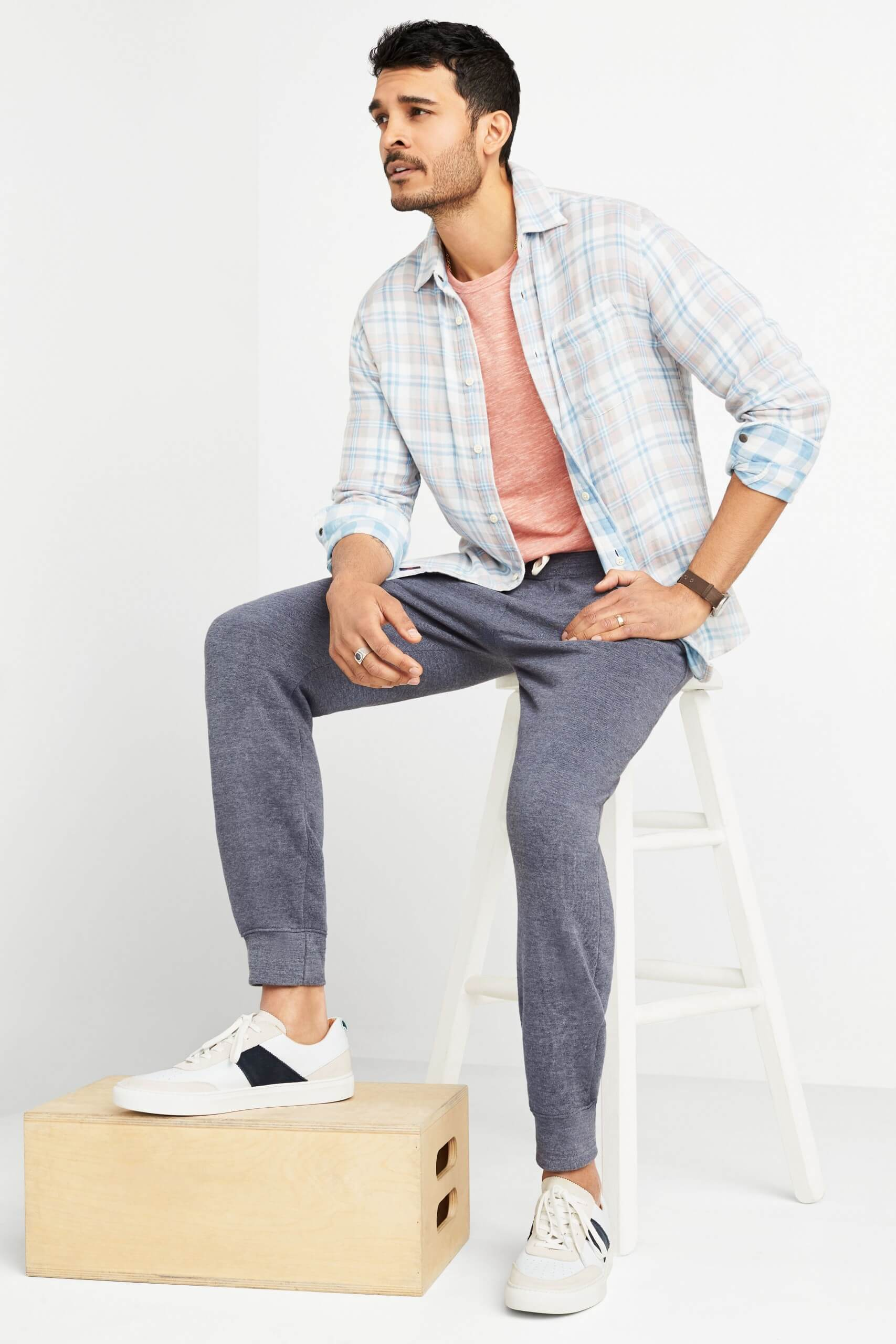 Stitch Fix Men's model sitting on a white stool wearing pink terry crew sweatshirt under a plaid button-down shirt with fleece pants and white sneakers.