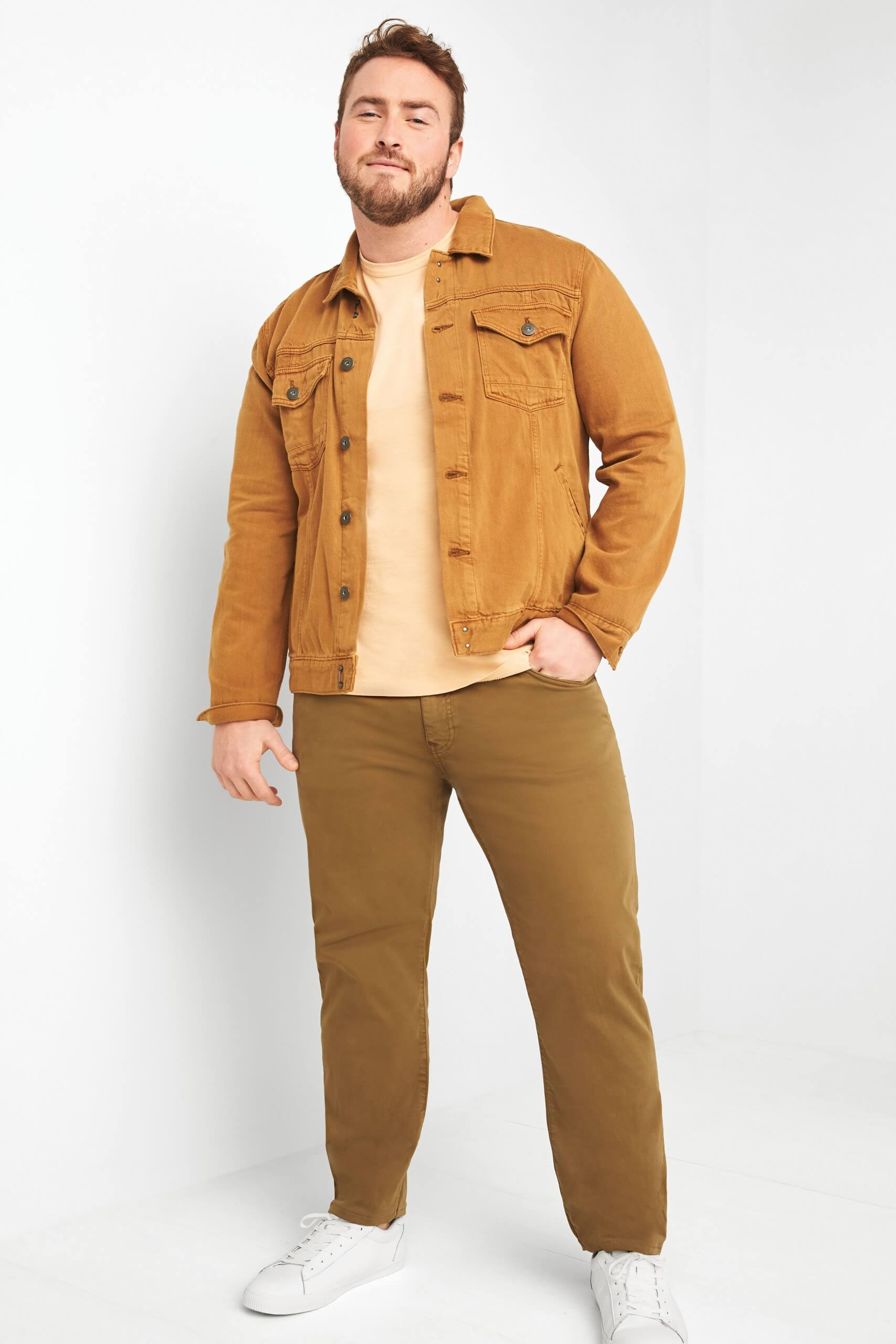 Stitch Fix Men's model wearing tan denim jacket over yellow t-shirt with brown pants and white sneakers.