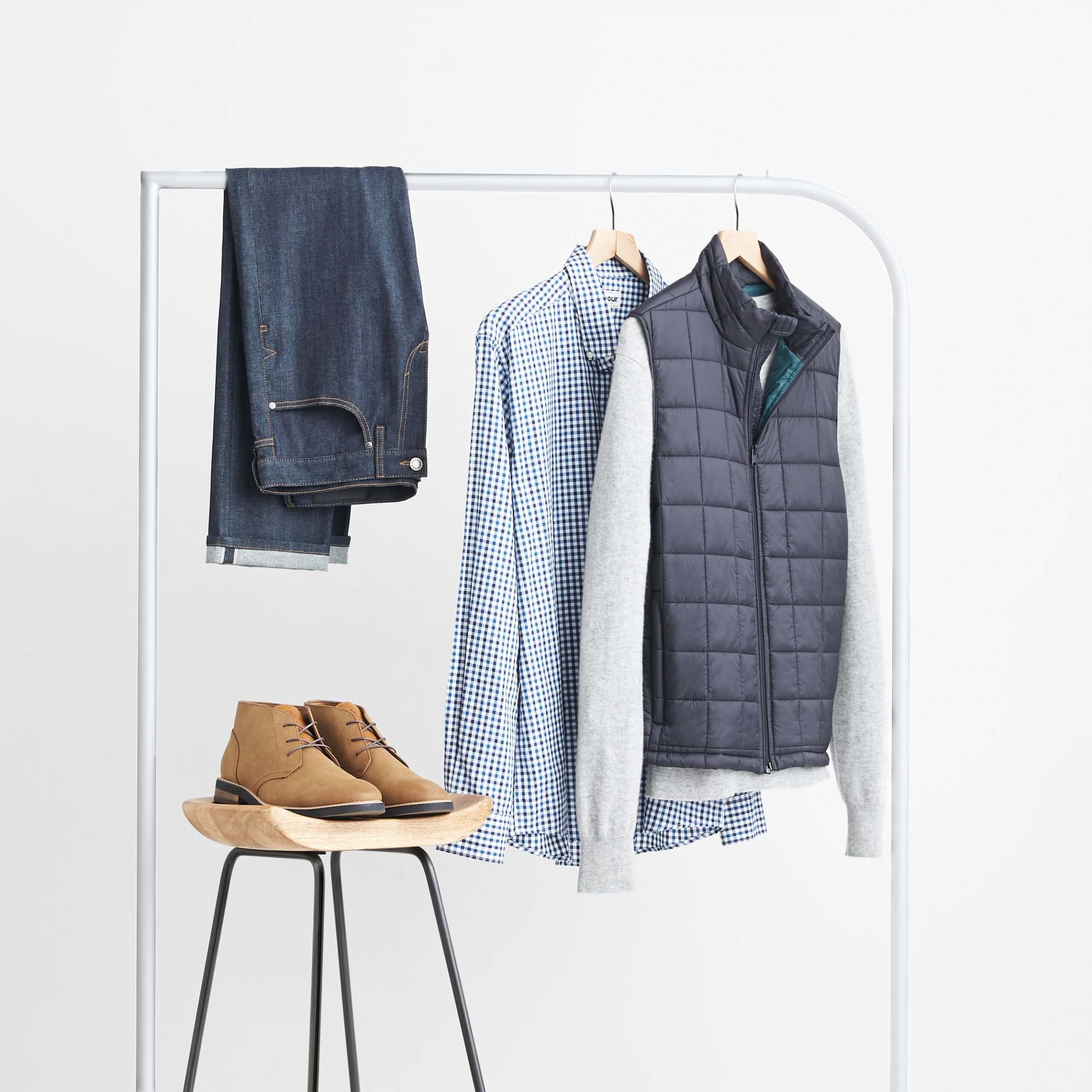 Stitch Fix Men's dark wash jeans, blue gingham button-down shirt, grey pullover and navy vest hanging on white rack next to brown chukkas on wooden stool.
