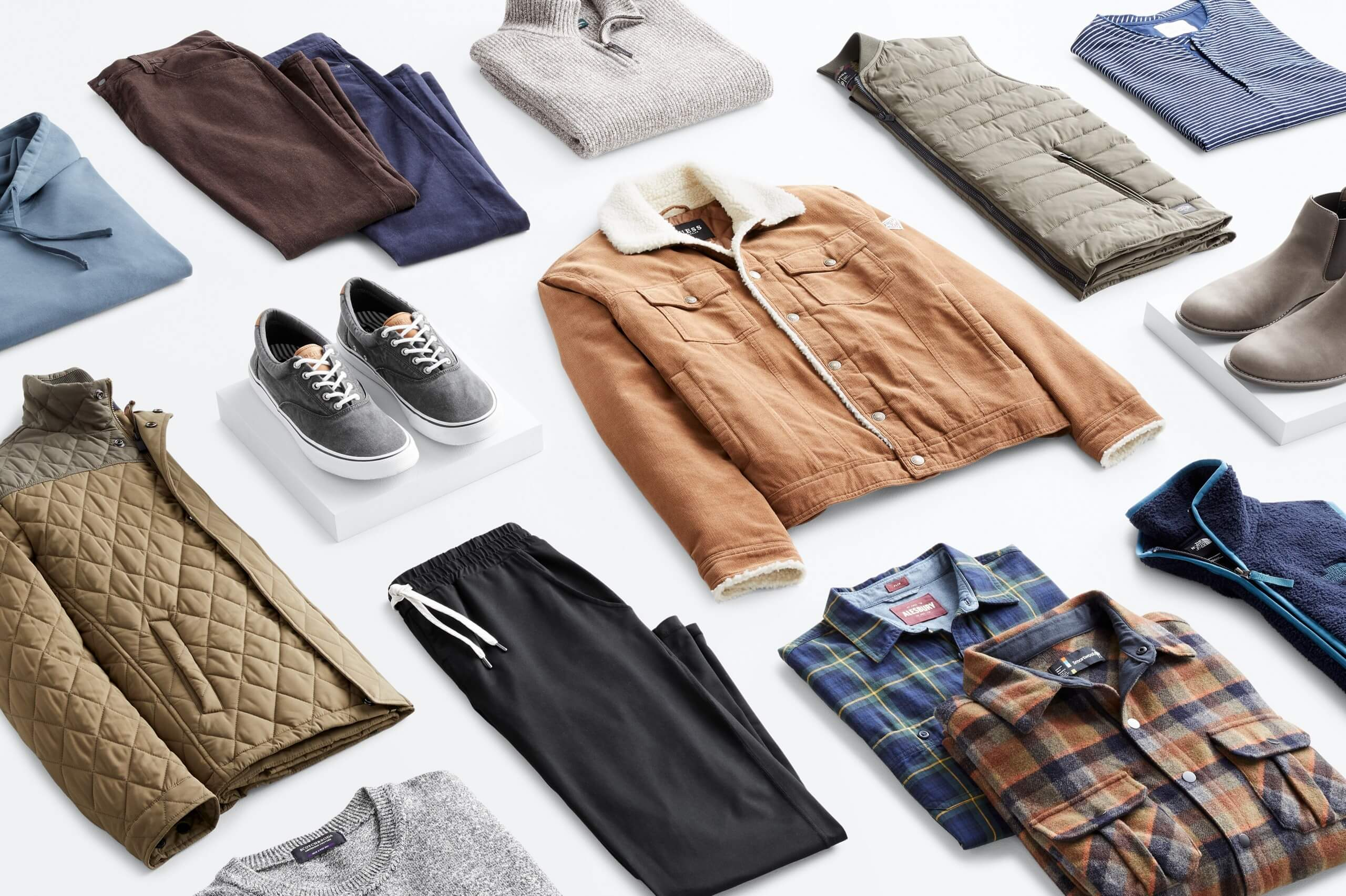 Stitch Fix Men's outfit laydown featuring a blue hoodie, brown pants, navy pants, grey quarter zip sweater, olive quilted jacket, grey sneakers, brown trucker jacket with sherpa collar, olive quilted vest, blue henley, grey crew neck tee, black joggers, plaid button downs in rusted orange and navy colors and navy blue vest.