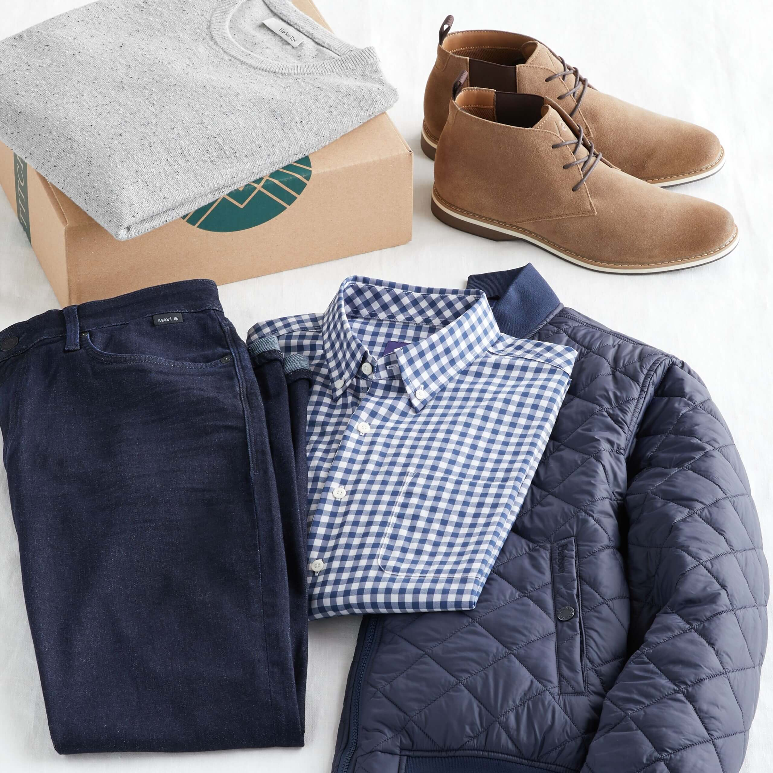 Stitch Fix Men's outfit laydown featuring grey pullover on Stitch Fix delivery box, next to brown chukkas, navy quilted jacket, blue collared button-down and dark wash jeans.