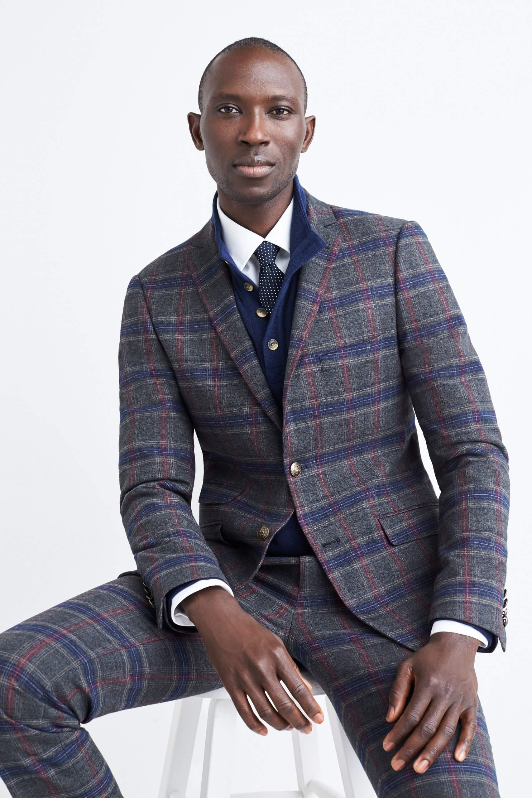 Stitch Fix Men's model sitting on a white stool wearing a navy plaid suit, white collared shirt and navy blue tie.
