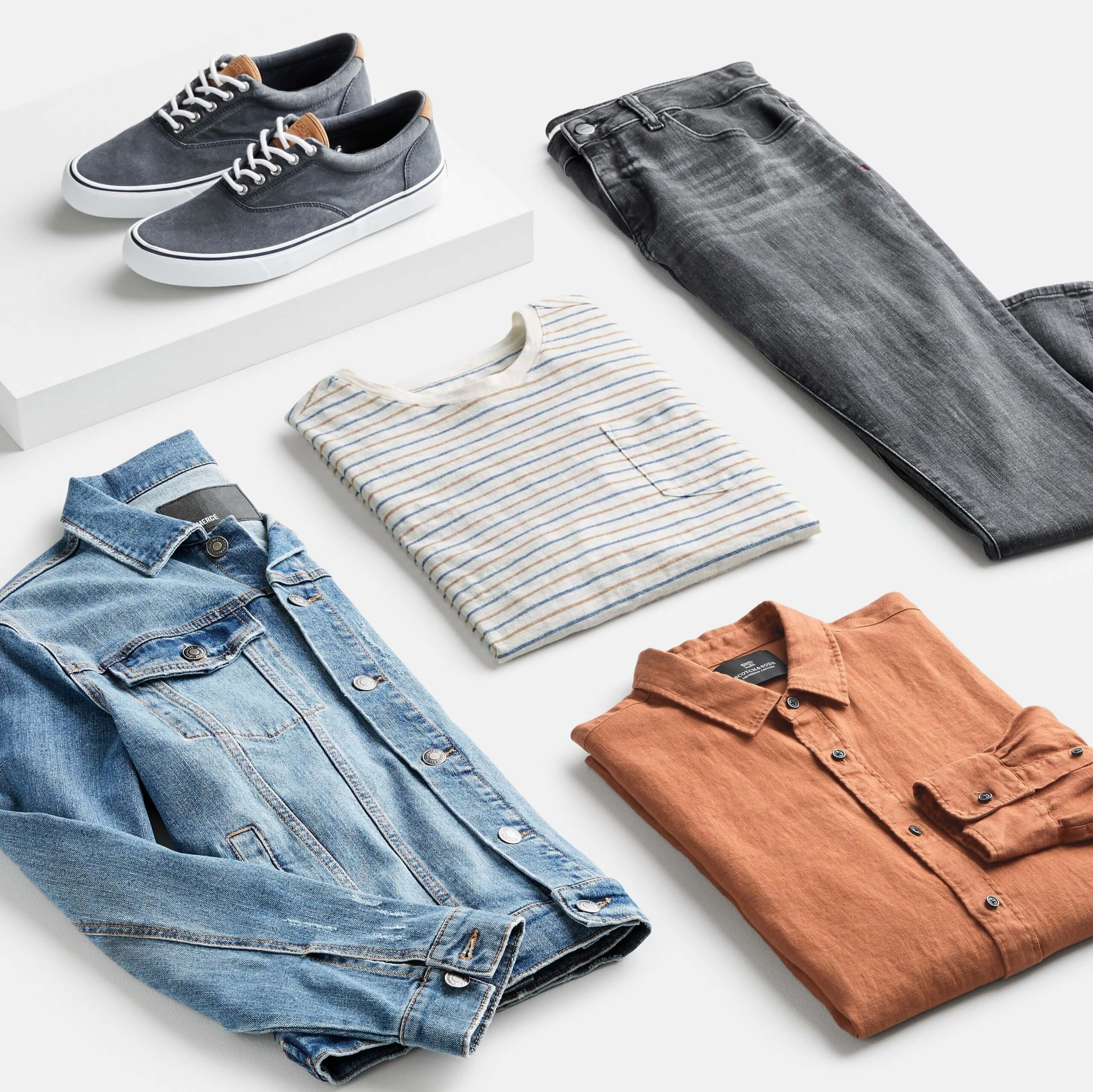 Stitch Fix Men's outfit laydown featuring grey lace-up sneakers on a white block, next to a denim jacket, grey, blue and orange striped crew neck t-shirt, orange button-down shirt and grey jeans.