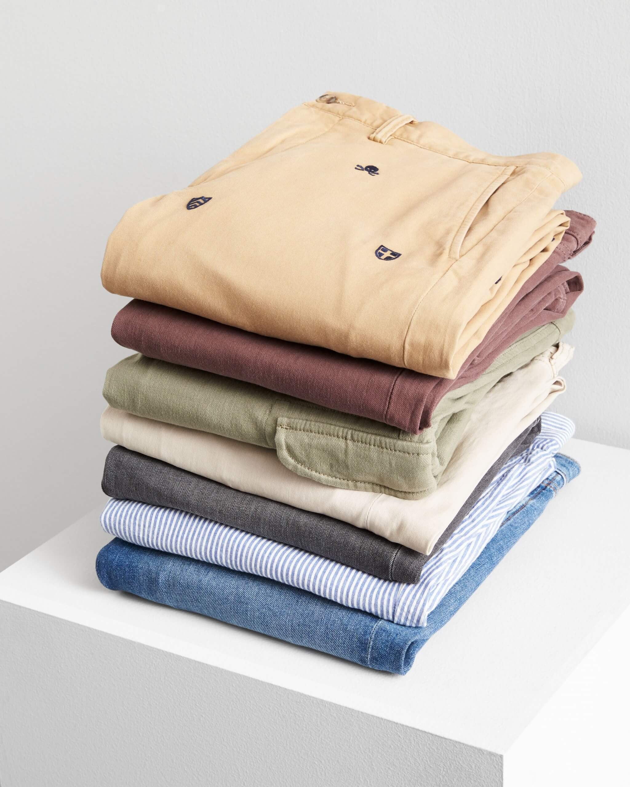 Stitch Fix Men's stack of slim pants in denim, olive, cream, burgundy and printed yellow pants on a white cube.